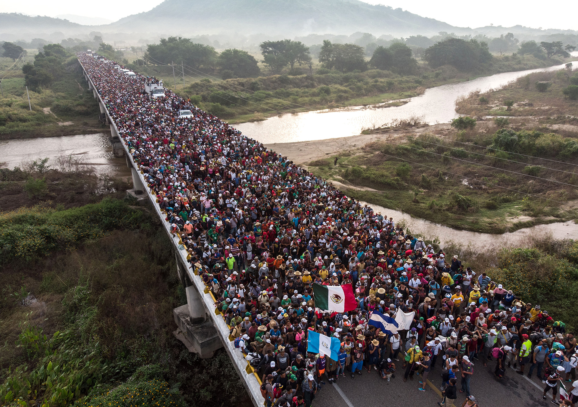 Una imagen aérea de la caravana migrante que había partido de Honduras, cruzando un puente camino a San Pedro Tapanatepec, en México, el 27 de octubre (Guillermo Arias / AFP)