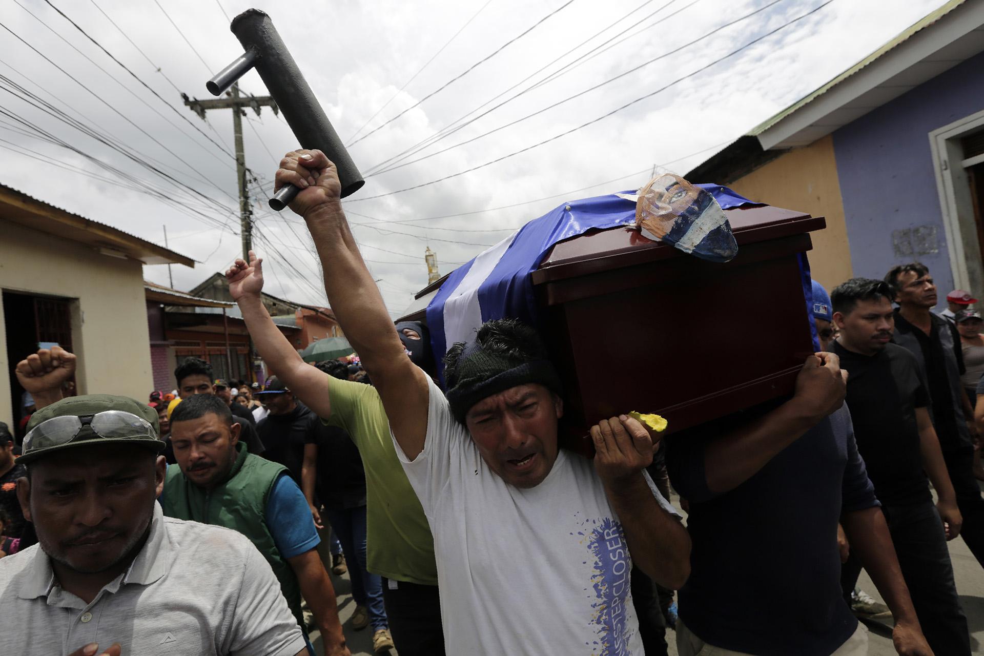Un amigo de Jorge Carrion, asesinado durante las protestas contra el gobierno de Daniel Ortega en Nicaragua, sostiene un mortero casero durante el funeral en la ciudad deMasaya, el 7 de junio (INTI OCON / AFP)