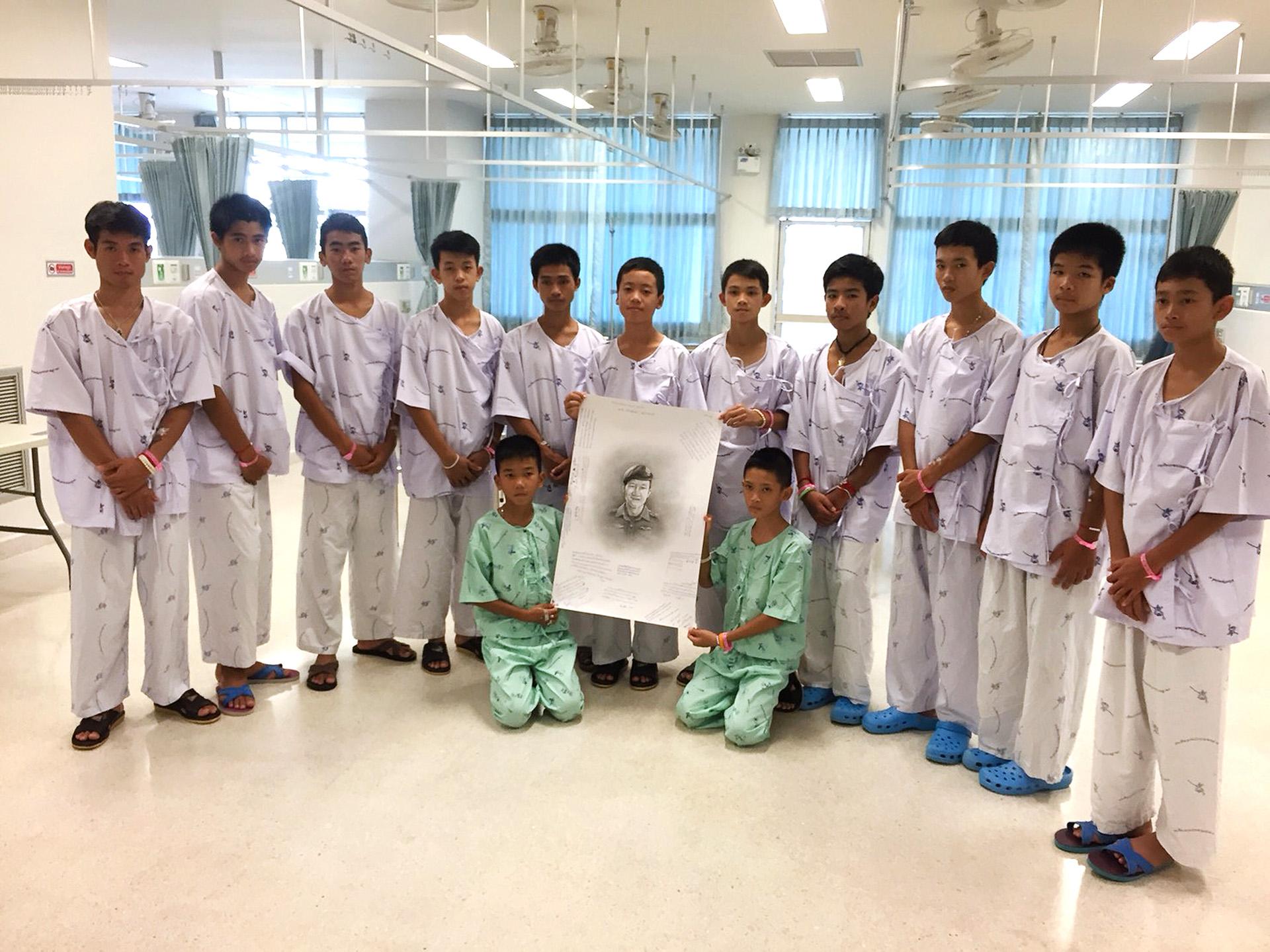 Los 12 niños y el entrenador rescatados en Tailandia tras pasar semanas atrapados en una cueva rinden un tributo al buzo fallecido durante el operativo, el 15 de julio en el HospitalChiang Rai Prachanukroh (AFP)