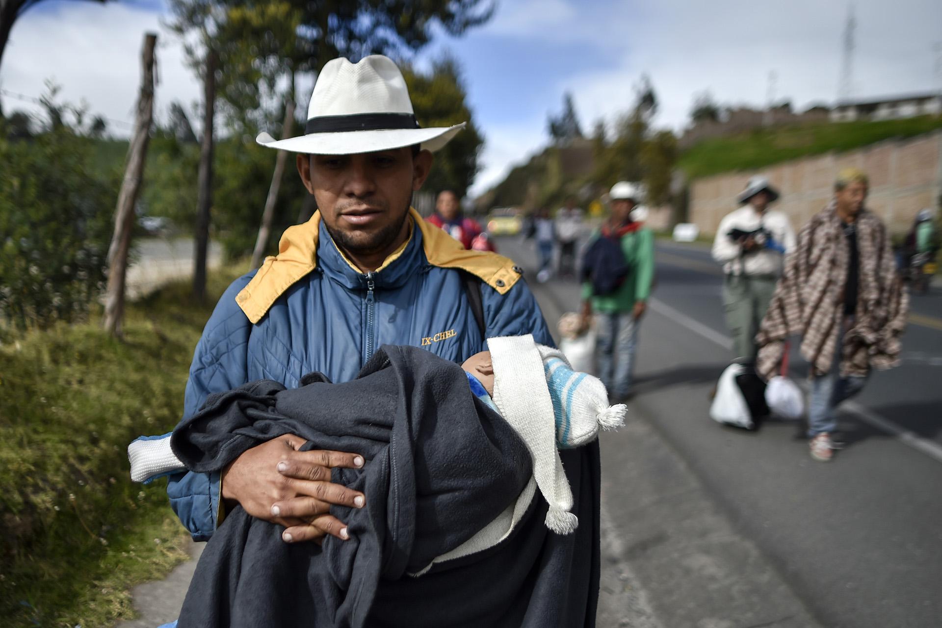 Richard Lomelly carga a su bebé Tiago mientras camina junto a otros cientos de venezolanos por la Autopista Panamericana en Colombia, rumbo a Perú, el 23 de agosto (Luis ROBAYO / AFP)