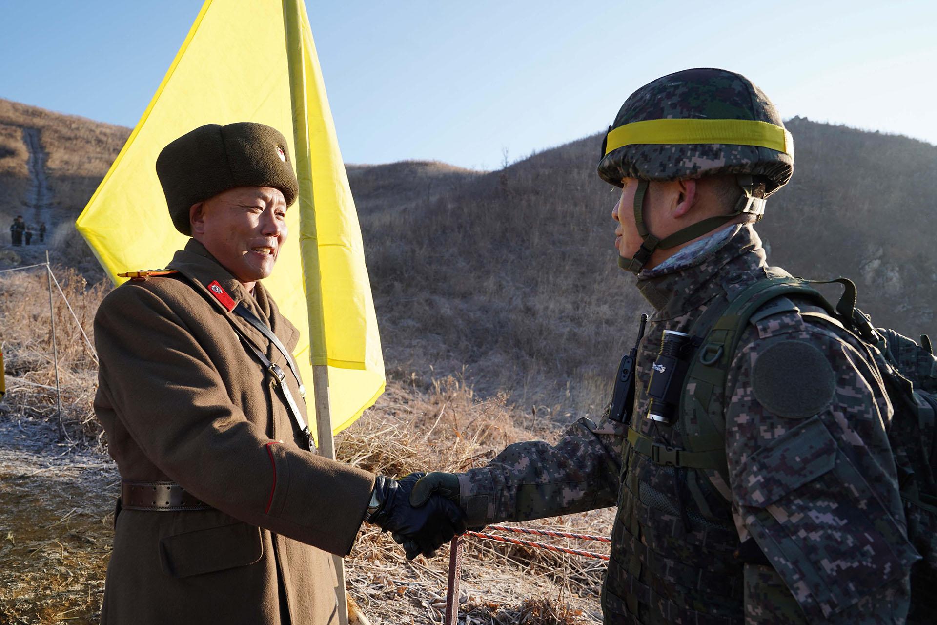 Soldado surcoreano (der.) estrechando la mano de un soldado norcoreano (izq.) antes de cruzar la Línea de Demarcación Militar para inspeccionar el puesto de guardia norcoreano desmantelado dentro de la zona desmilitarizada (DMZ) que divide las dos Coreas en Cheorwon. (AFP)
