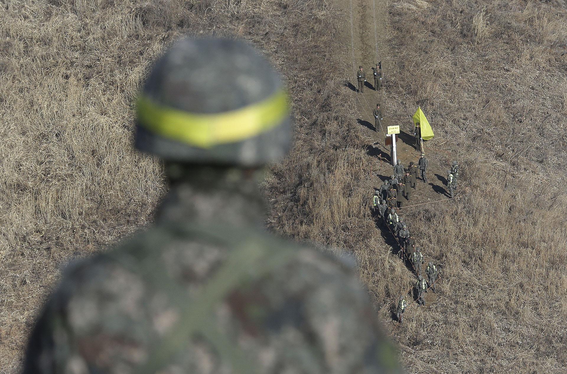 Soldados norcoreanos (arriba) son recibidos por soldados surcoreanos antes de cruzar la Línea de Demarcación Militar dentro de la Zona Desmilitarizada (DMZ) en Cheorwon. (AFP)