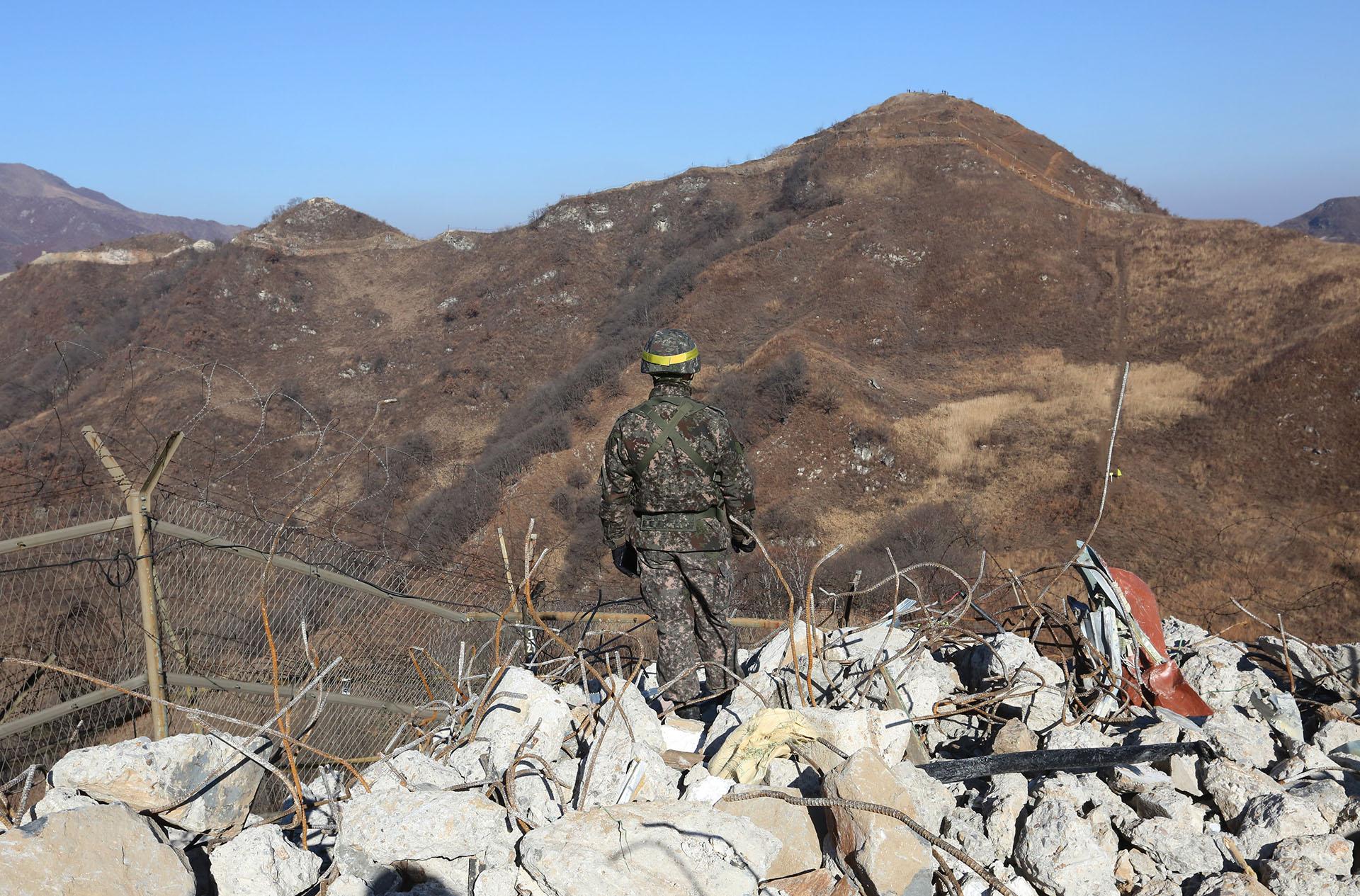 Un soldado del ejército surcoreano hace guardia en el puesto fronterizo desmantelado dentro de la Zona Desmilitarizada (DMZ) en la sección central de la frontera intercoreana en Cheorwon, Corea del Sur, el 12 de diciembre de 2018. (AFP)