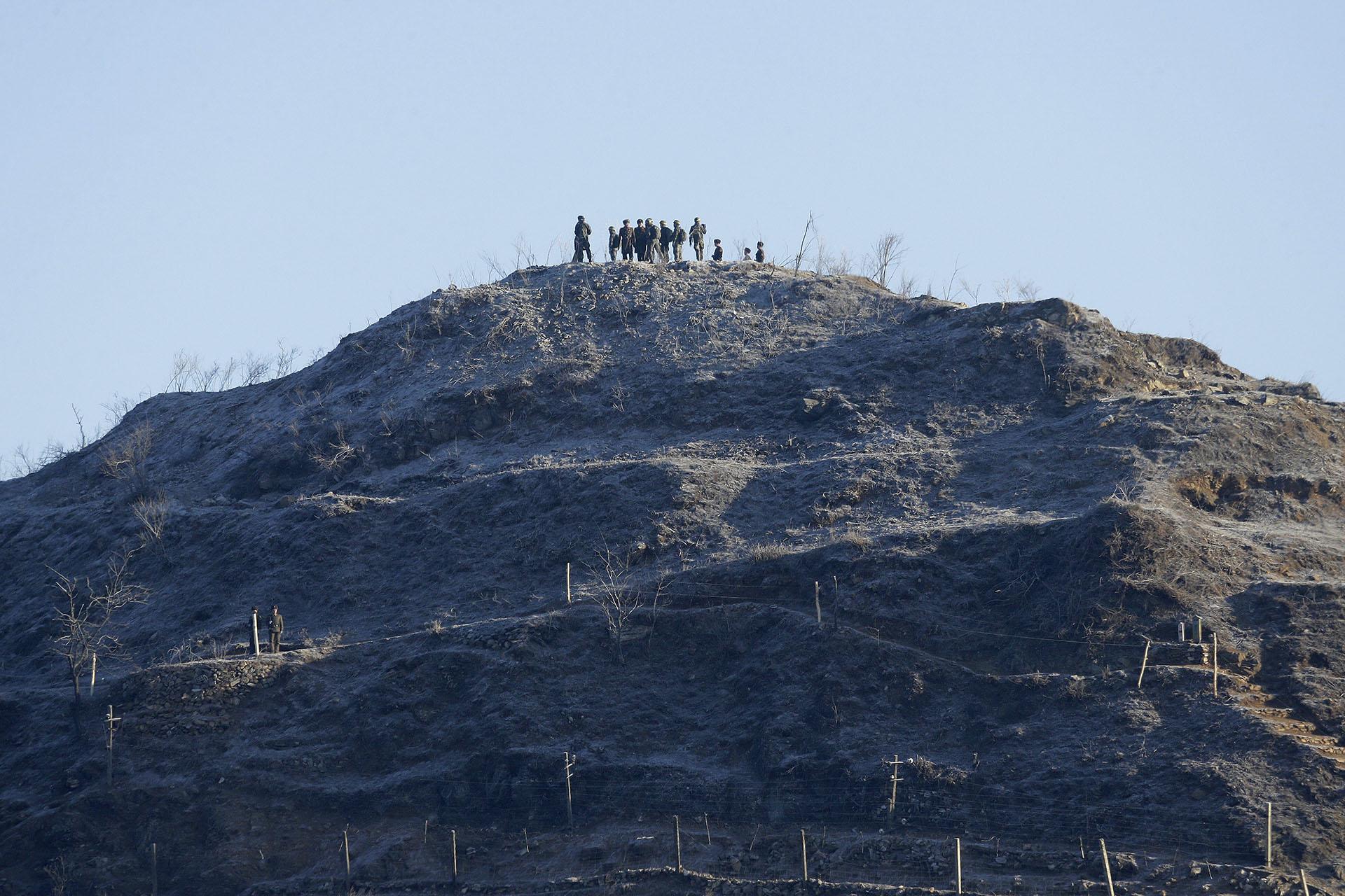 Soldados del ejército de Corea del Sur (con cintas amarillas en la cabeza) y sus homólogos de Corea del Norte inspeccionan el desmantelado puesto de guardia de Corea del Norte dentro de la Zona Desmilitarizada (DMZ) en la sección central de la frontera intercoreana en Cheorwon, Corea del Sur, el 12 de diciembre de 2018. (AFP)