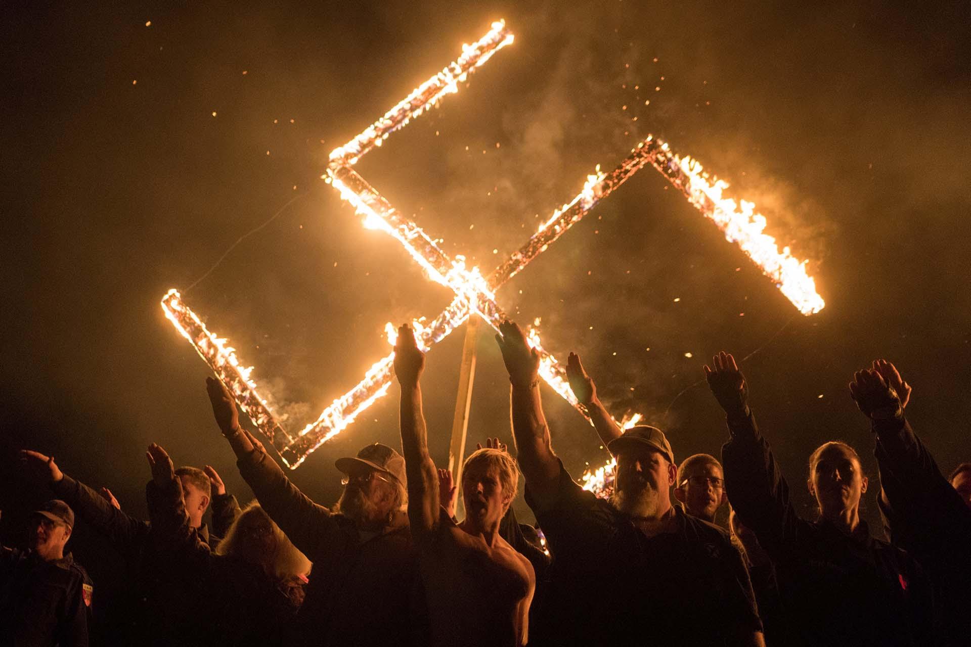 Miembros del Movimiento Nacional Socialista, un grupo político de supremacistas blancos, realiza el saludo nazi junto a una esvástica en llamasen una locaciónno reveladaenGeorgia, Estados Unidos, el 21 de abril de 2018 (REUTERS/Go Nakamura)