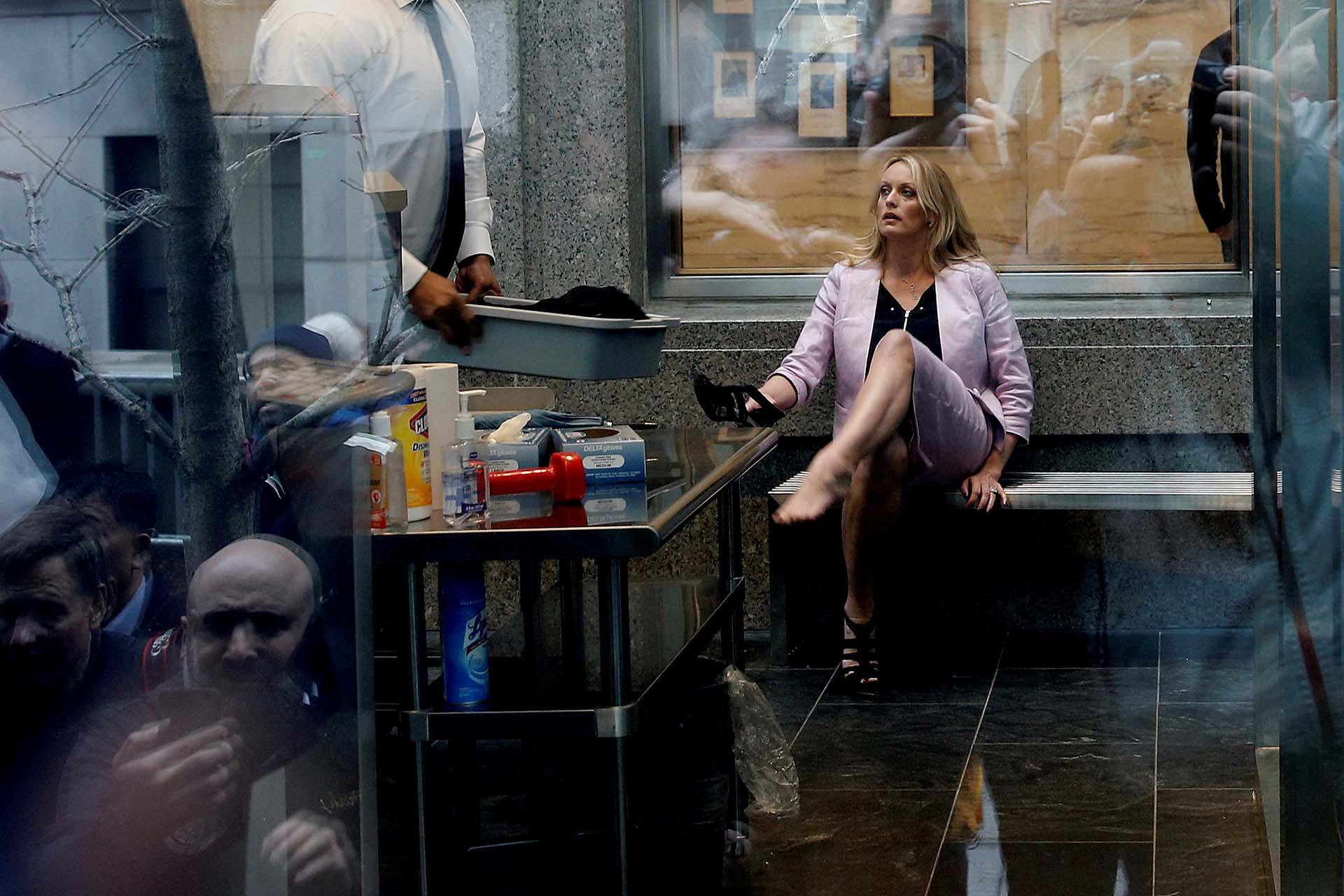 La actriz porno Stormy Daniels, quien afirma que tuvo relaciones sexuales con Trump en 2006, se quita los zapatospara pasar por un control de seguridad en una corte federal de Manhattanante la mirada de unos 50 fotógrafos desplegados tras un vallado policial (REUTERS/Shannon Stapleton)