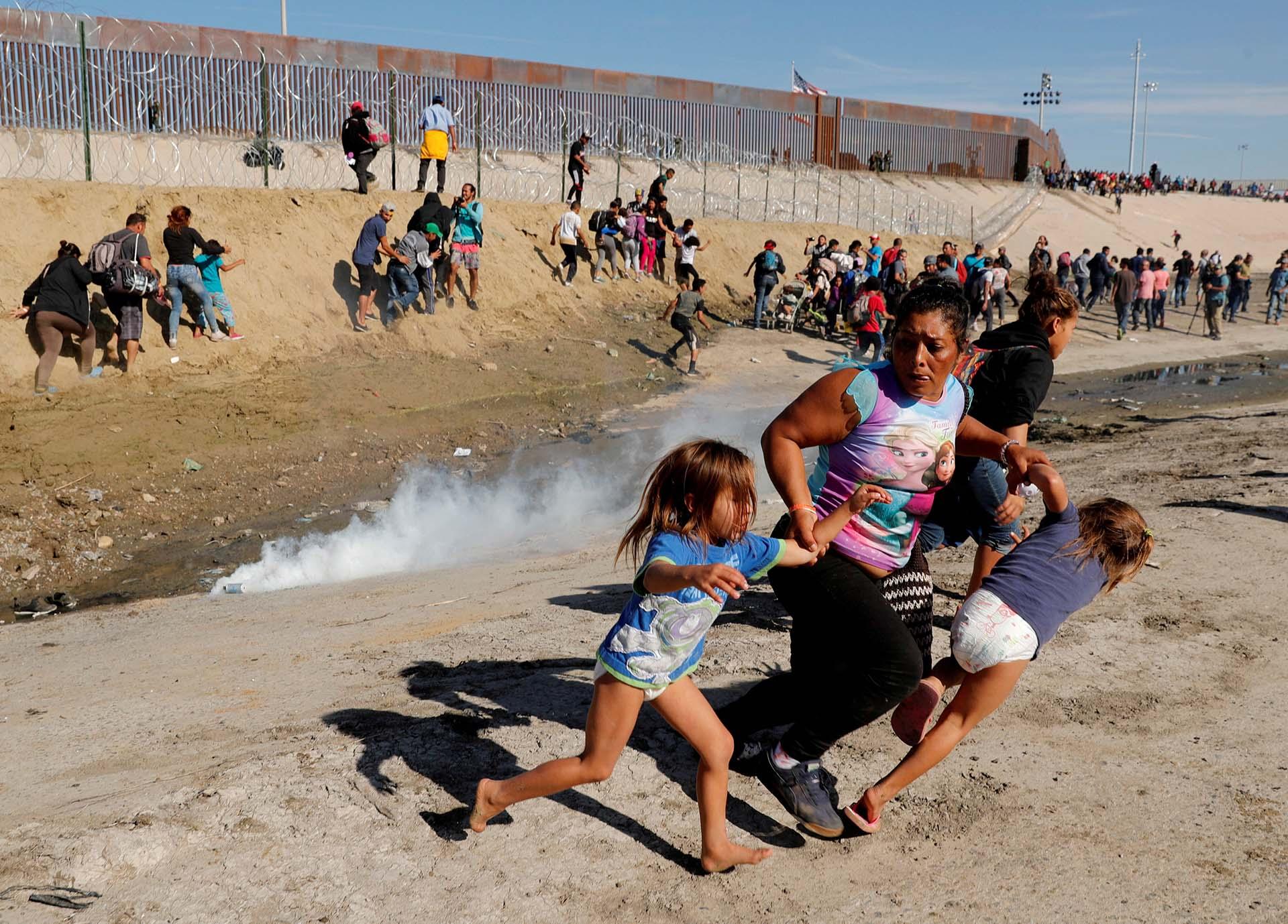 La hondureña María Meza, de 40 años, huye con sus hijas de los gases lacrimógenos lanzados por fuerzas estadounidenses contra la caravana migrante el 25 de noviembre de 2018 frente al muro fronterizo instalado en Tijuana, México(REUTERS/Kim Kyung-Hoon/File Photo)
