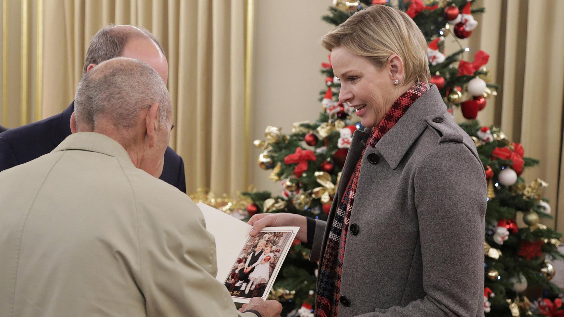 Charlene sonríe orgullosa mientras muestra una postal navideña con la fotografía de sus hijos, los príncipes Jacques y Gabriella