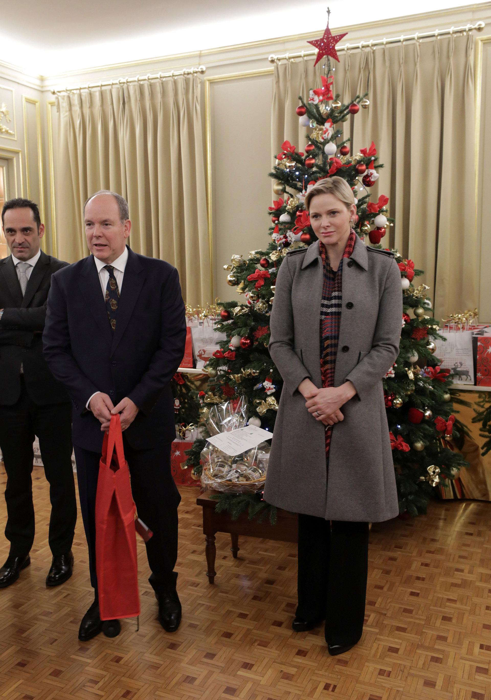 Alberto de Mónaco y su mujer Charlene junto al árbol de Navidad, antes de repartir los regalos