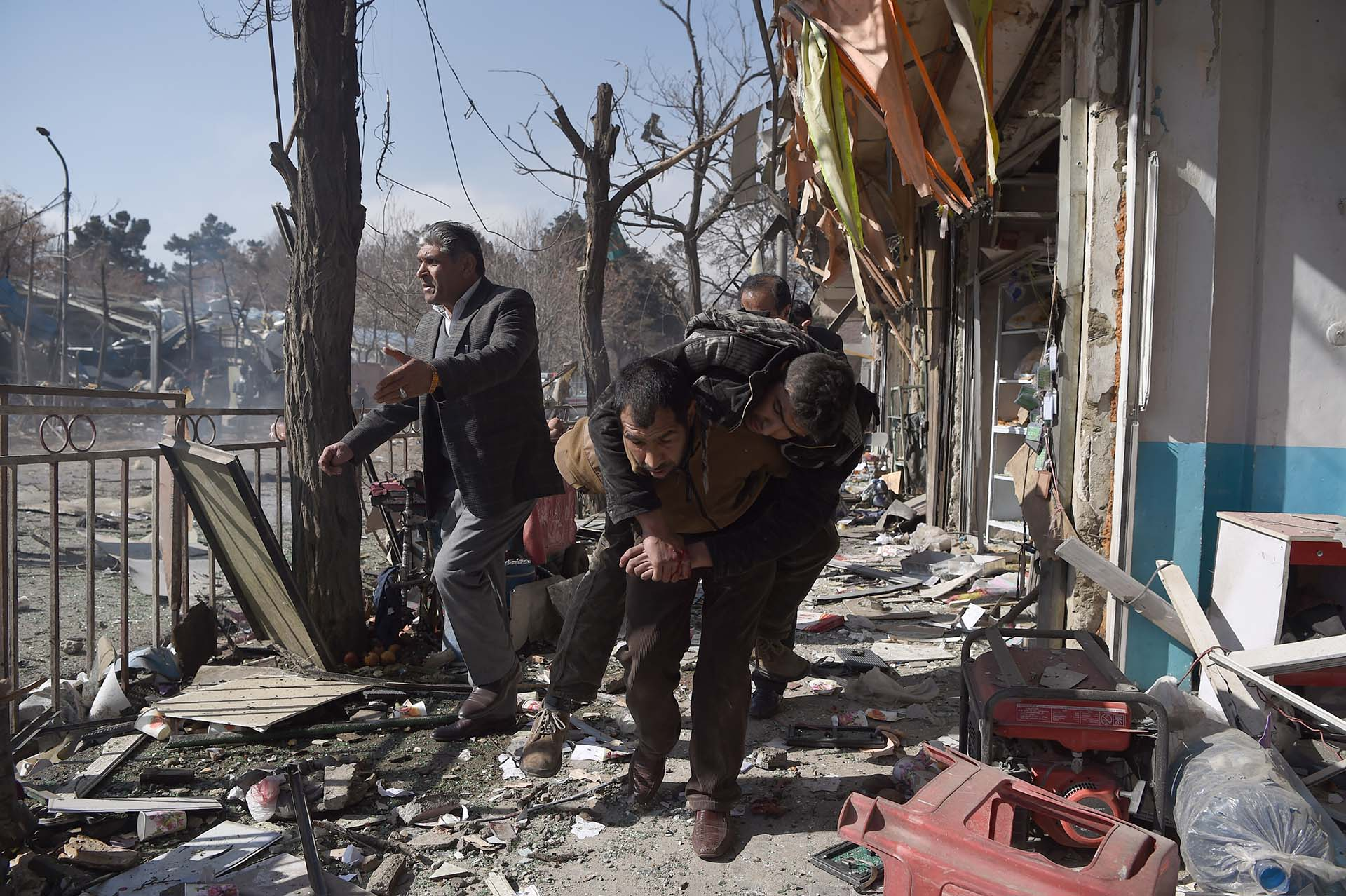 Voluntarios afganos cargan el cuerpo de una víctima de un coche bomba que explotó frente al Ministerio del Interior en Kabul el 27 de enero