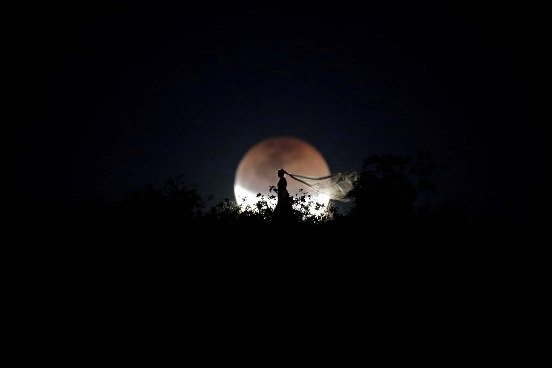 Una novia posa para una foto durante un eclipse lunar total en Brasilia, Brasil, el 27 de julio