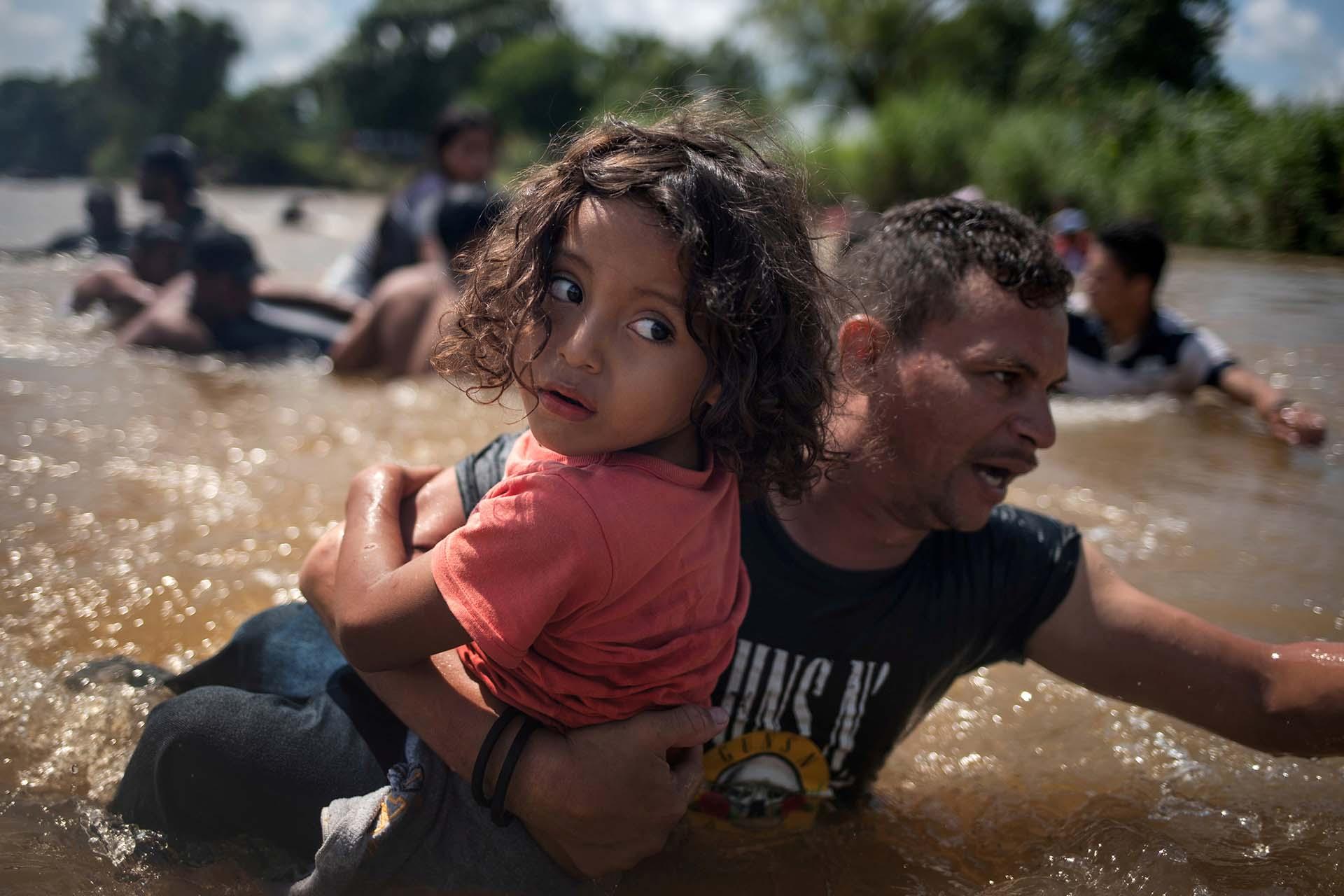 Luis Acosta sostiene como puede al pequeño Ángel Jesús, de 5 años. Ambos son de Honduras e intentan cruzar el río Suchiate a México desde Guatemala, el 29 de octubre, con el objetivo final de llegar a los EEUU