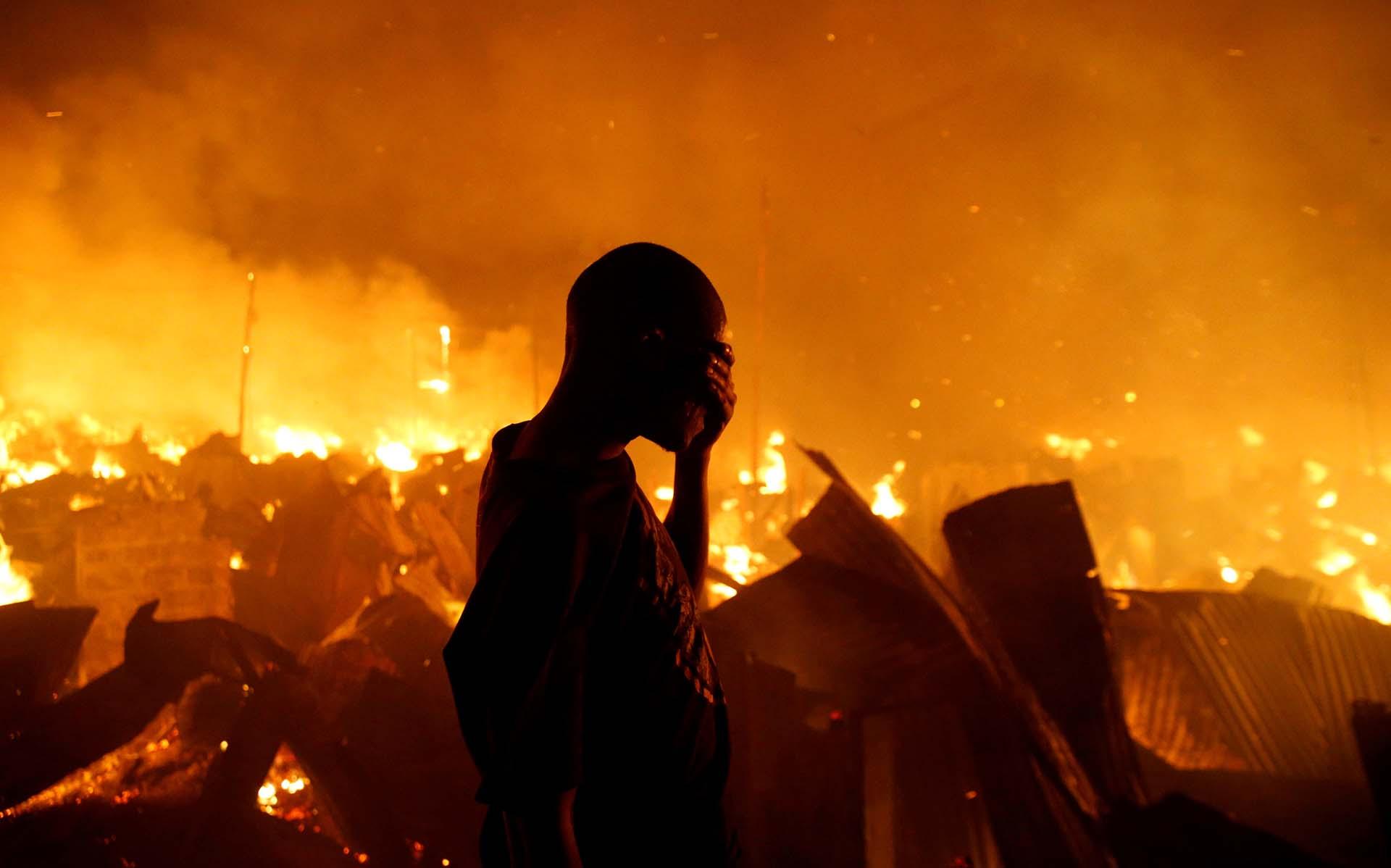Un residente sufre frente al incendio en la favela de Kijiji en el sur de Nairobi, en Kenia, el 28 de enero