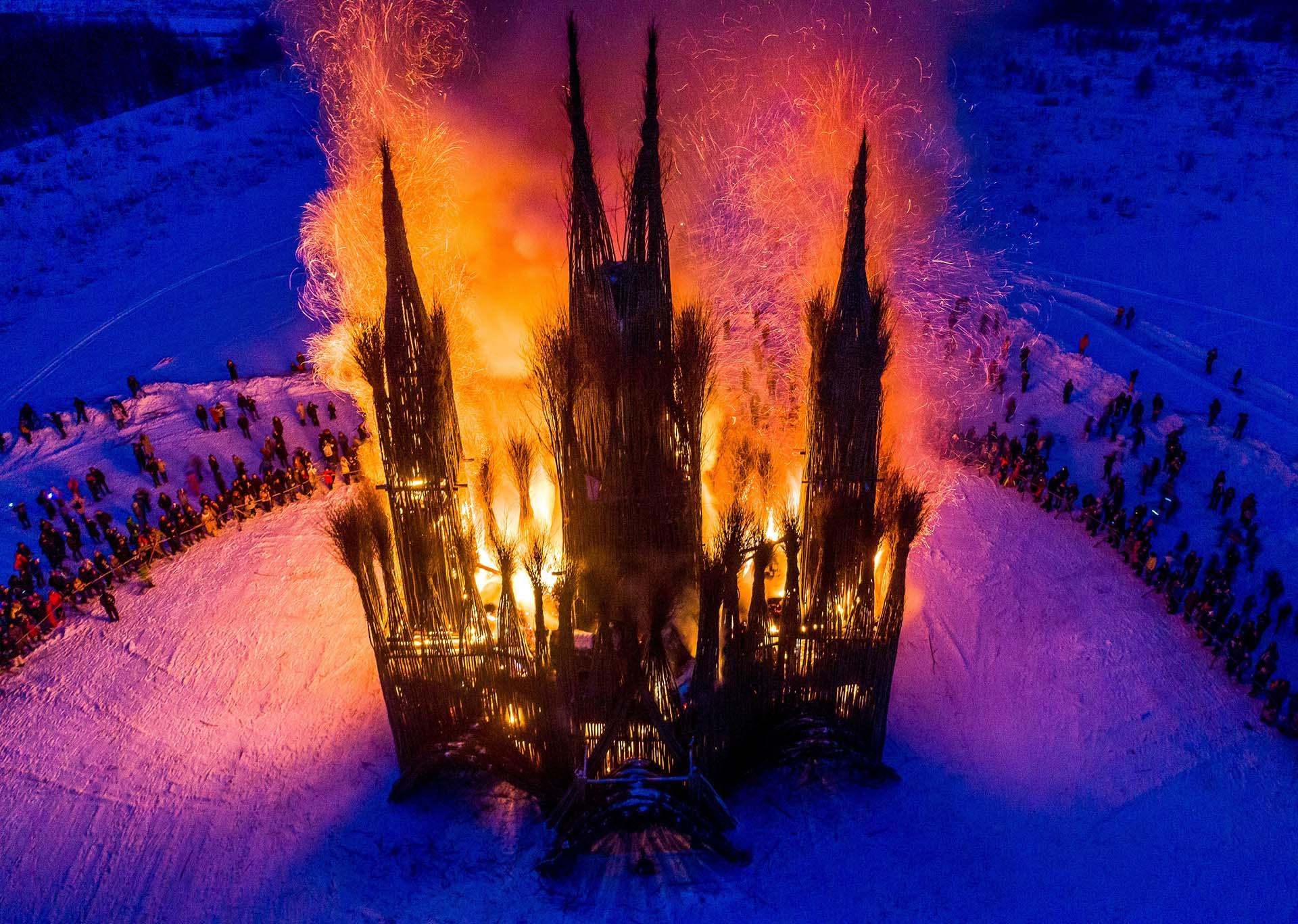 Espectadores observan la quema de una escultura del artista ruso Nikolay Polissky durante la celebración del Shrovetide (Maslenitsa) en el pueblo de Nikola-Lenivets, a unos 200 kilómetros de Moscú, el 17 de febrero