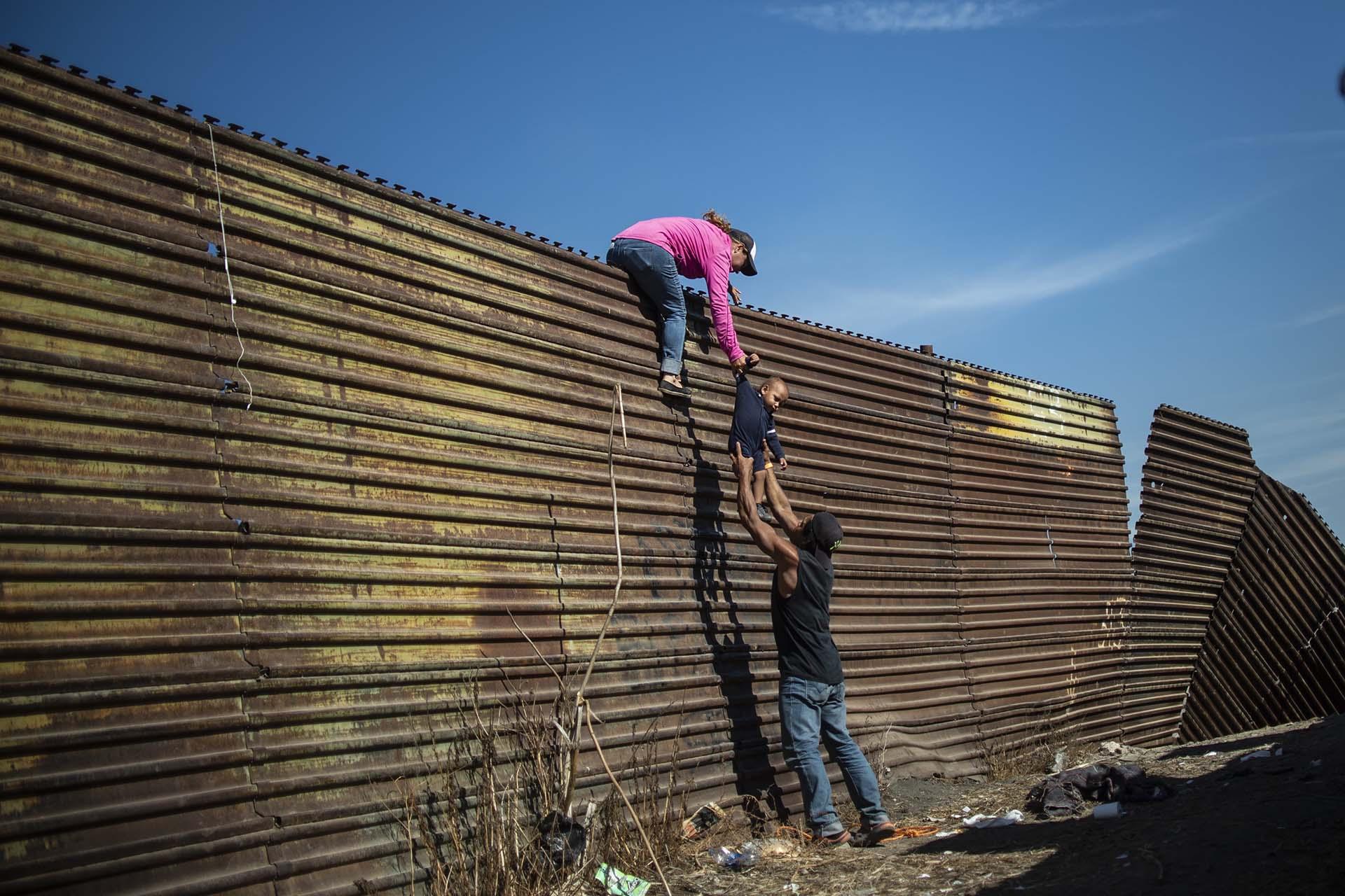 Un grupo de migrantes centroamericanos trepa la valla fronteriza entre México y EEUUcerca del paso fronterizo de El Chaparral, en Tijuana, el 25 de noviembre