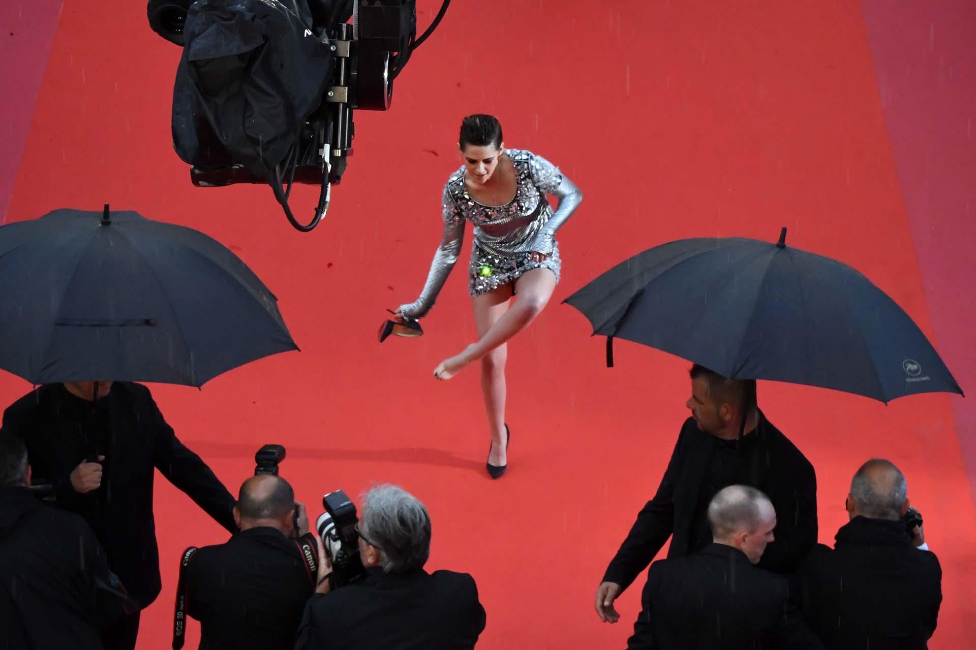 La actriz estadounidense Kristen Stewart se quita un zapato en la alfombra roja al llegar a la 71.ª edición del festival de Cannes el 14 de mayo