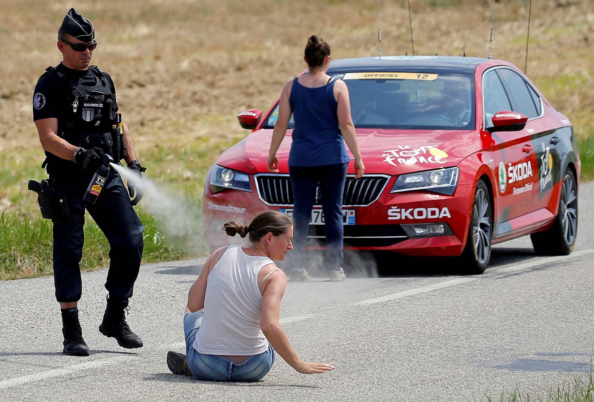Un policía lanza gas pimienta a una manifestante mientras otra se para frente al automóvil de la transmisión del Tour de France durante una protesta el 24 de julio