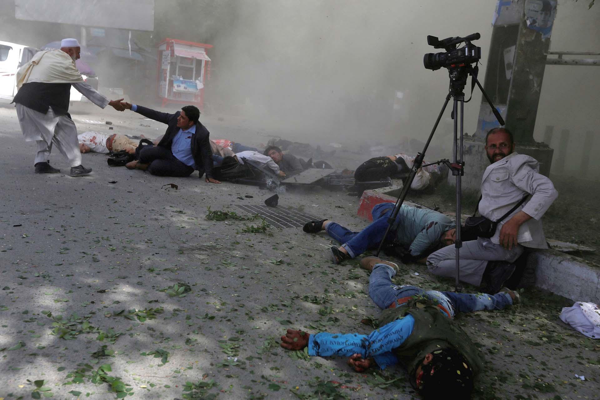 Periodistas afganos después de dos atentados suicidas del Estado Islámico que dejaron 29 muertos en el centro de Kabul el 20 de abril