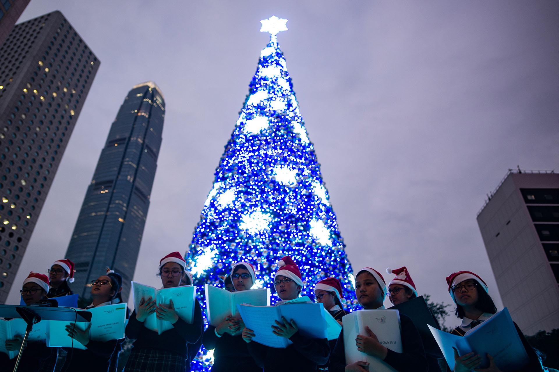 El coro de jóvenes de un colegio canta junto al árbol navideño en el distrito central de Hong Kong (Photo by Philip FONG / AFP)