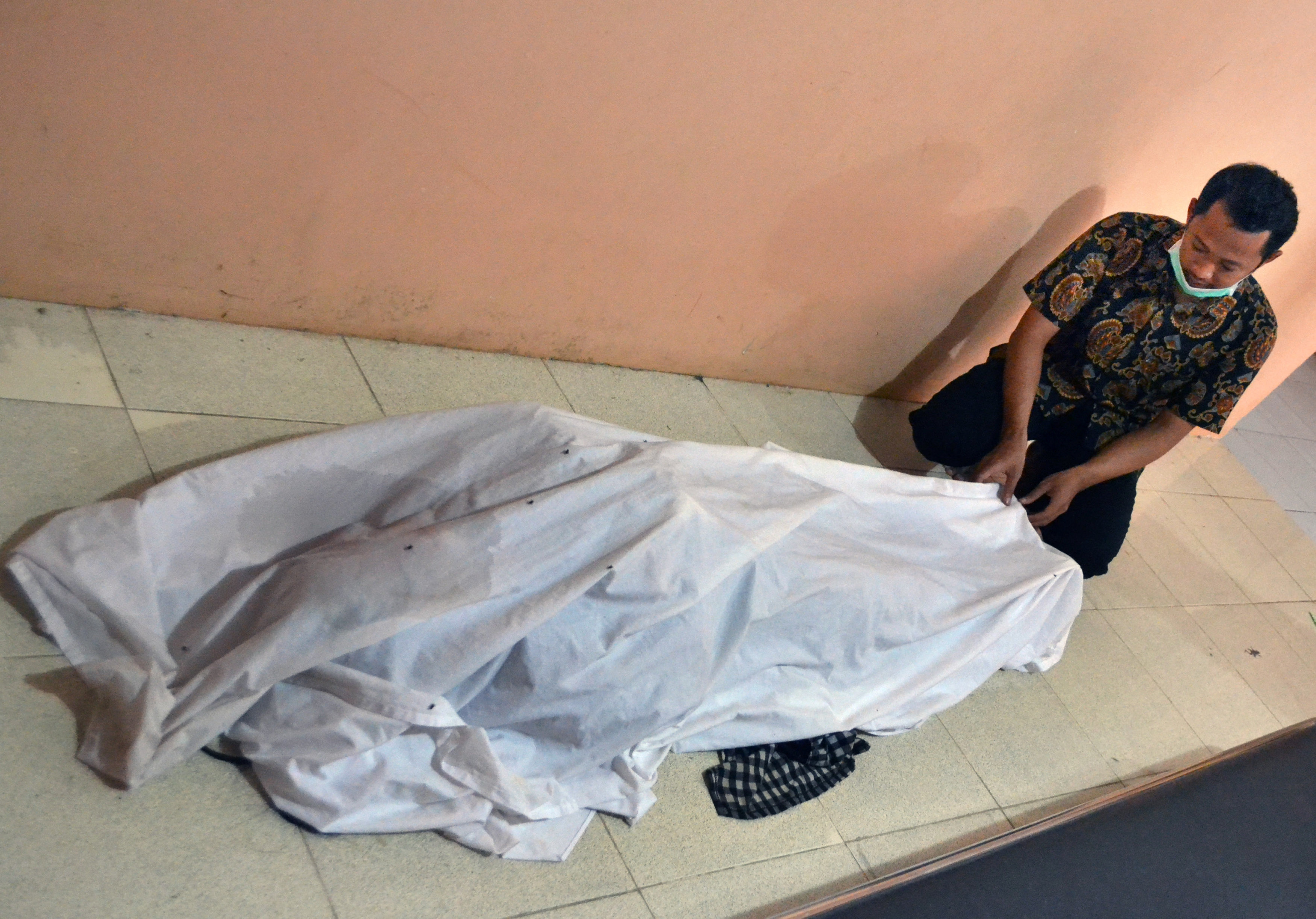 Un hombre cubre el cuerpo de una víctima. (Antara Foto/Muhammad Bagus Khoirunas/ via REUTERs)