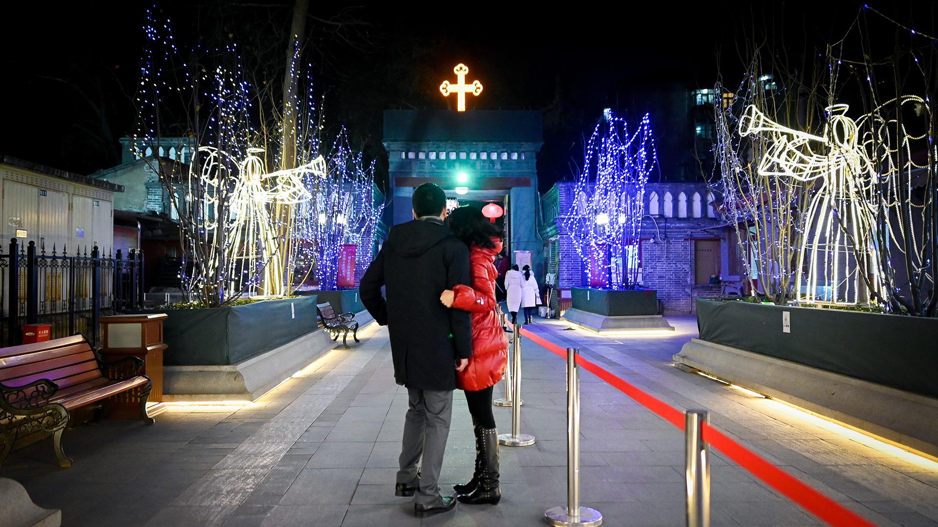 Una pareja de toma una fotografía mientras se preparan para entrar a misa en la iglesia católica de Beijing, China