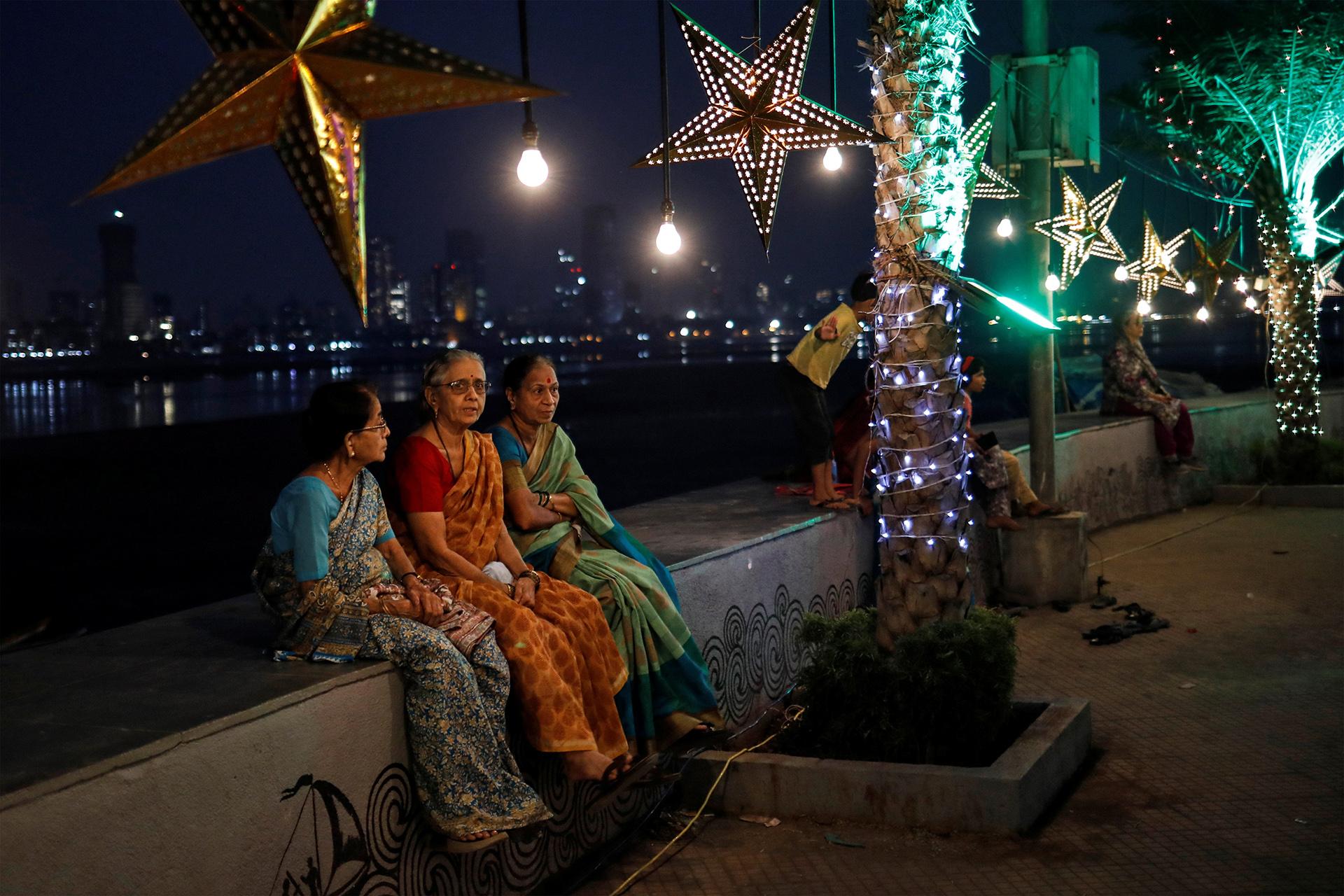En India, tres personas aguardan la llegada de la medianoche en en Mumbai