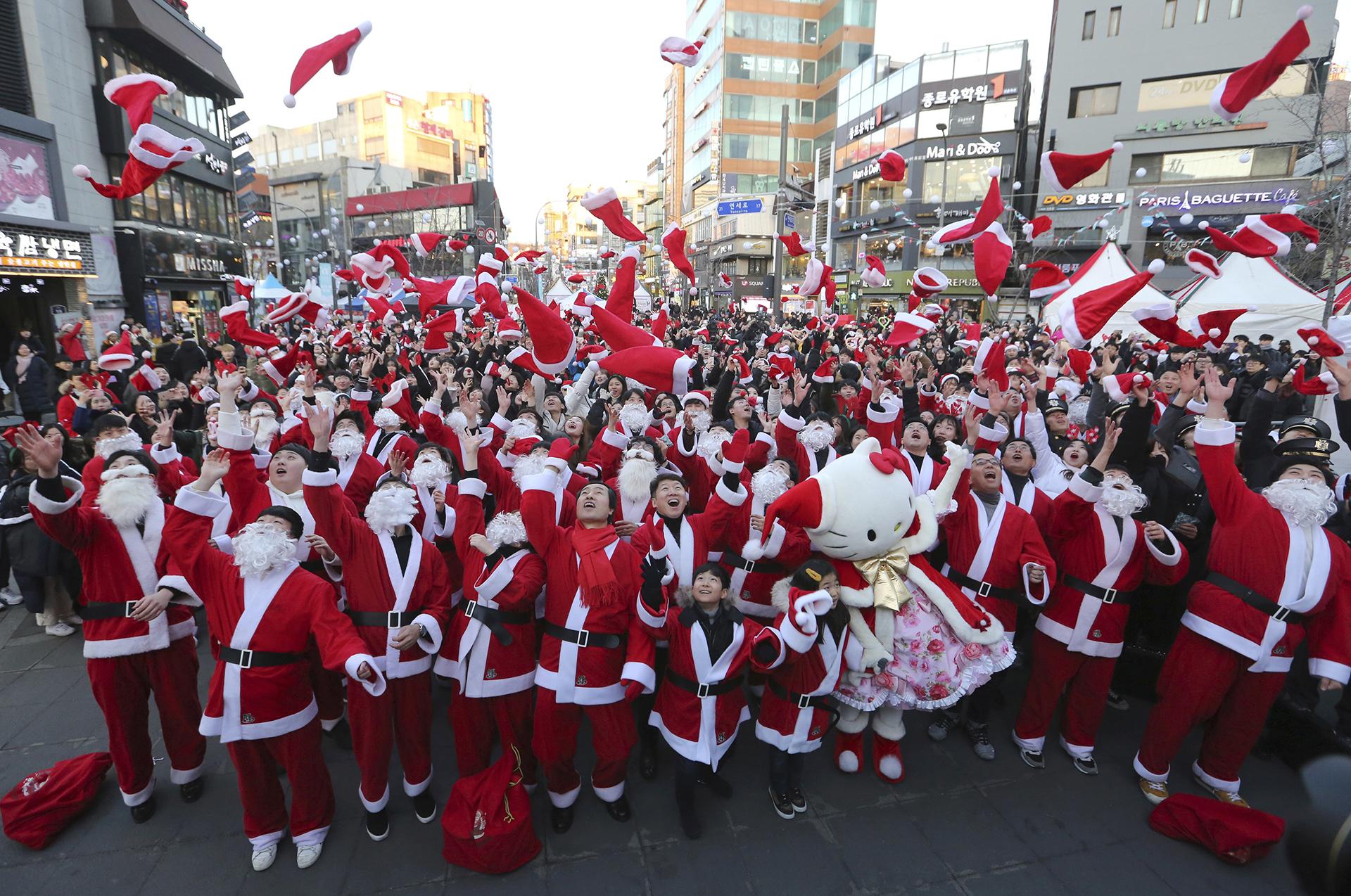 Voluntarios disfrazados de papá Noel arrojan sus sombreros en el centro de Seúl, Corea del Sur