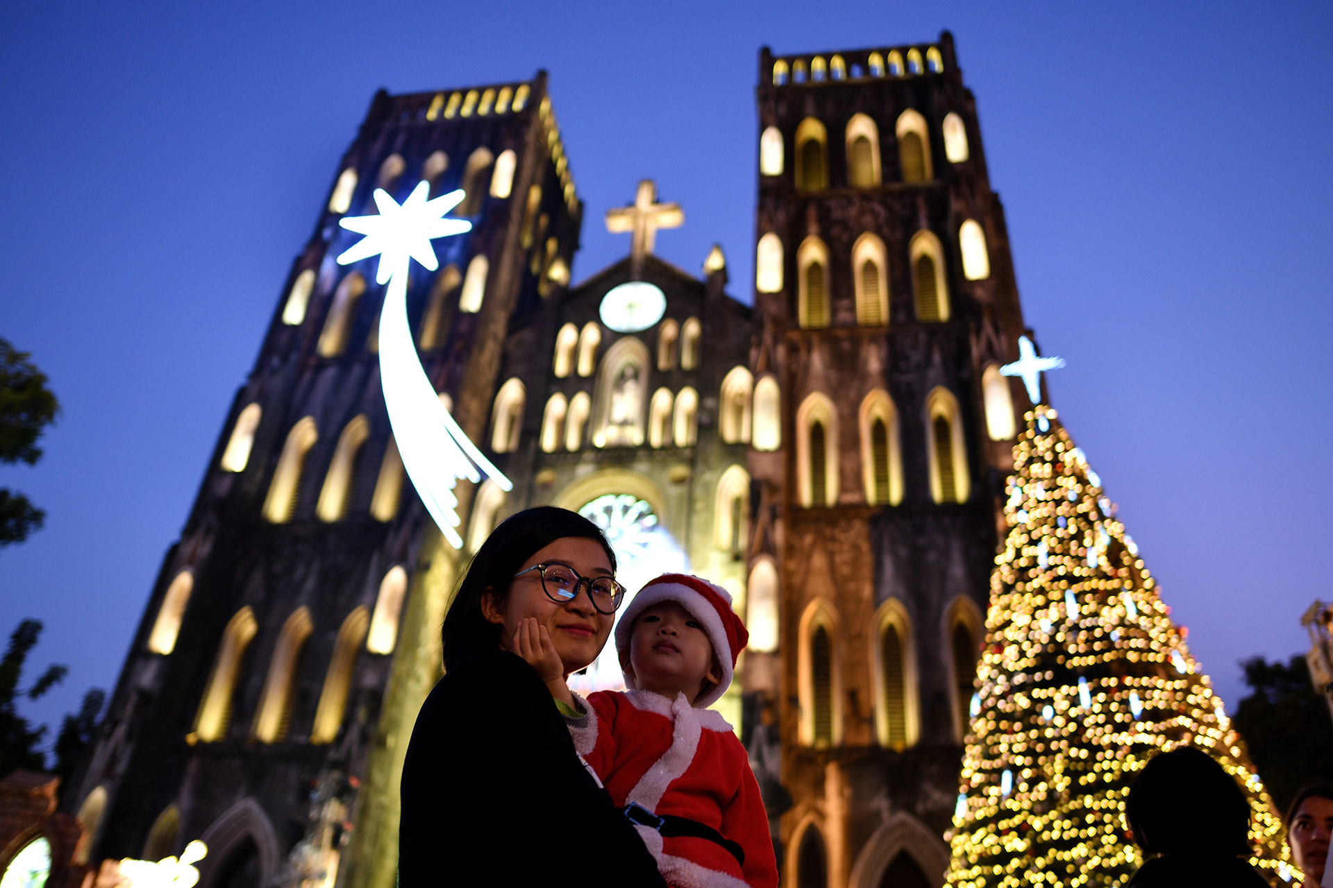 Una mujer vietnamita y su hijo vestido como un pequeño papá Noelfrente a la catedral de San José en Hanoi