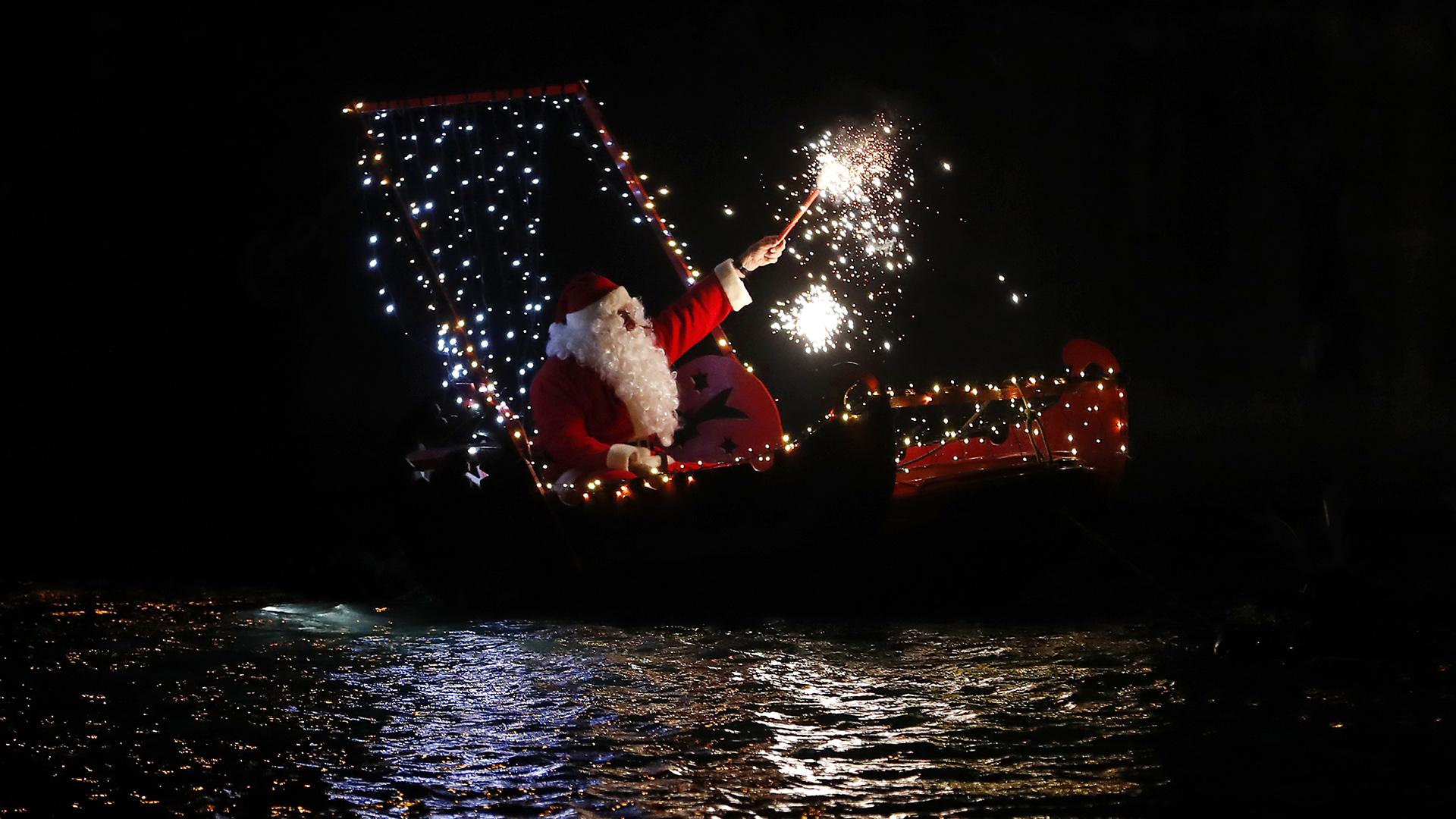 Un hombre disfrazado de Papá Noel sostiene una bengala mientras se sienta en un bote durante las celebraciones de la víspera de Navidad en Imperia, Italia