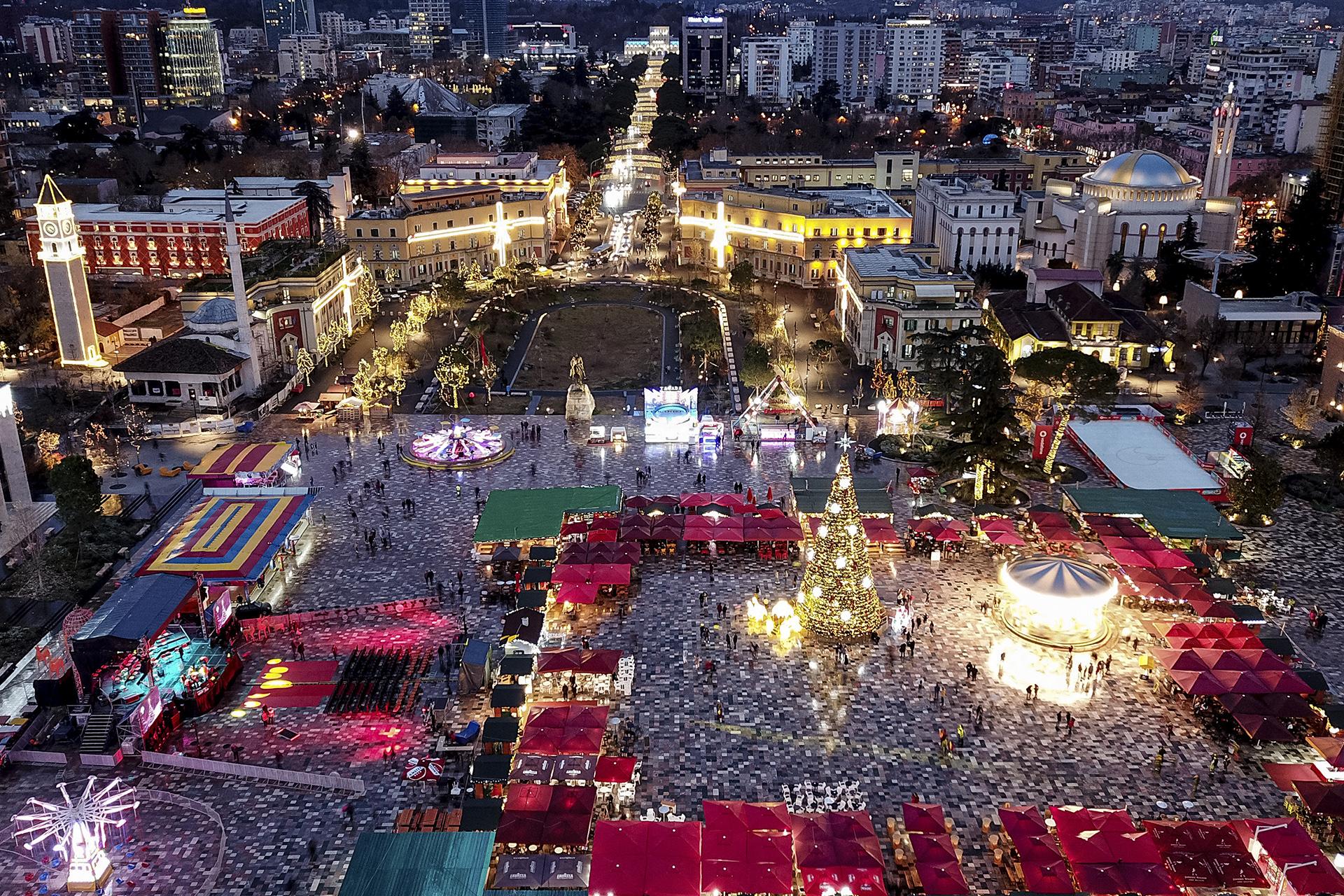 Vista aérea de la plaza principal de Tirana iluminada con adornos navideños y rodeada por un mercado navideño abierto.