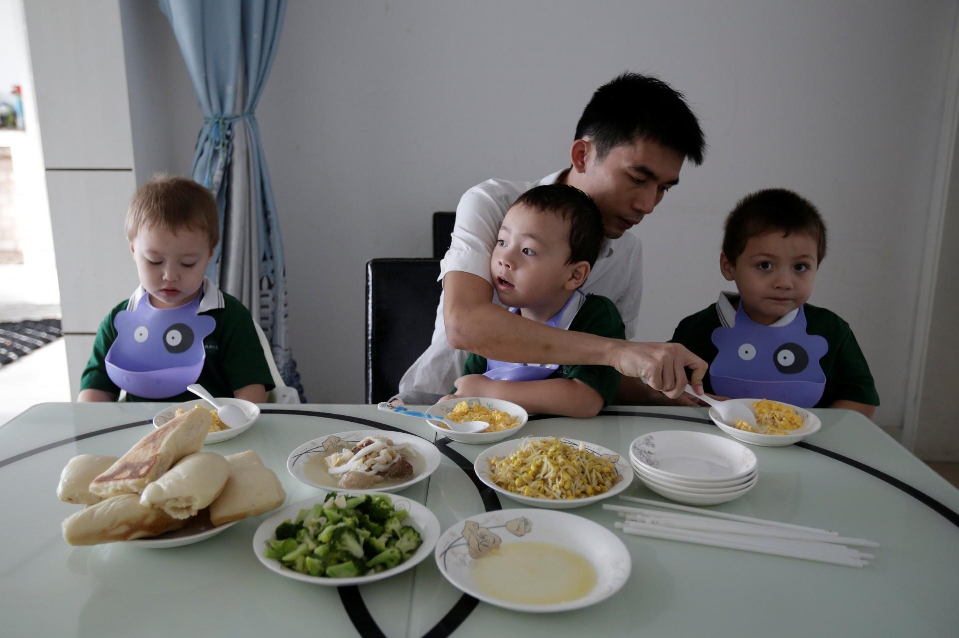La parejade An Hui, Ye Jianbin, ayuda a sus trillizos . An Zhiya, An Zhizhong y An Zhifei desayunan en su casa,