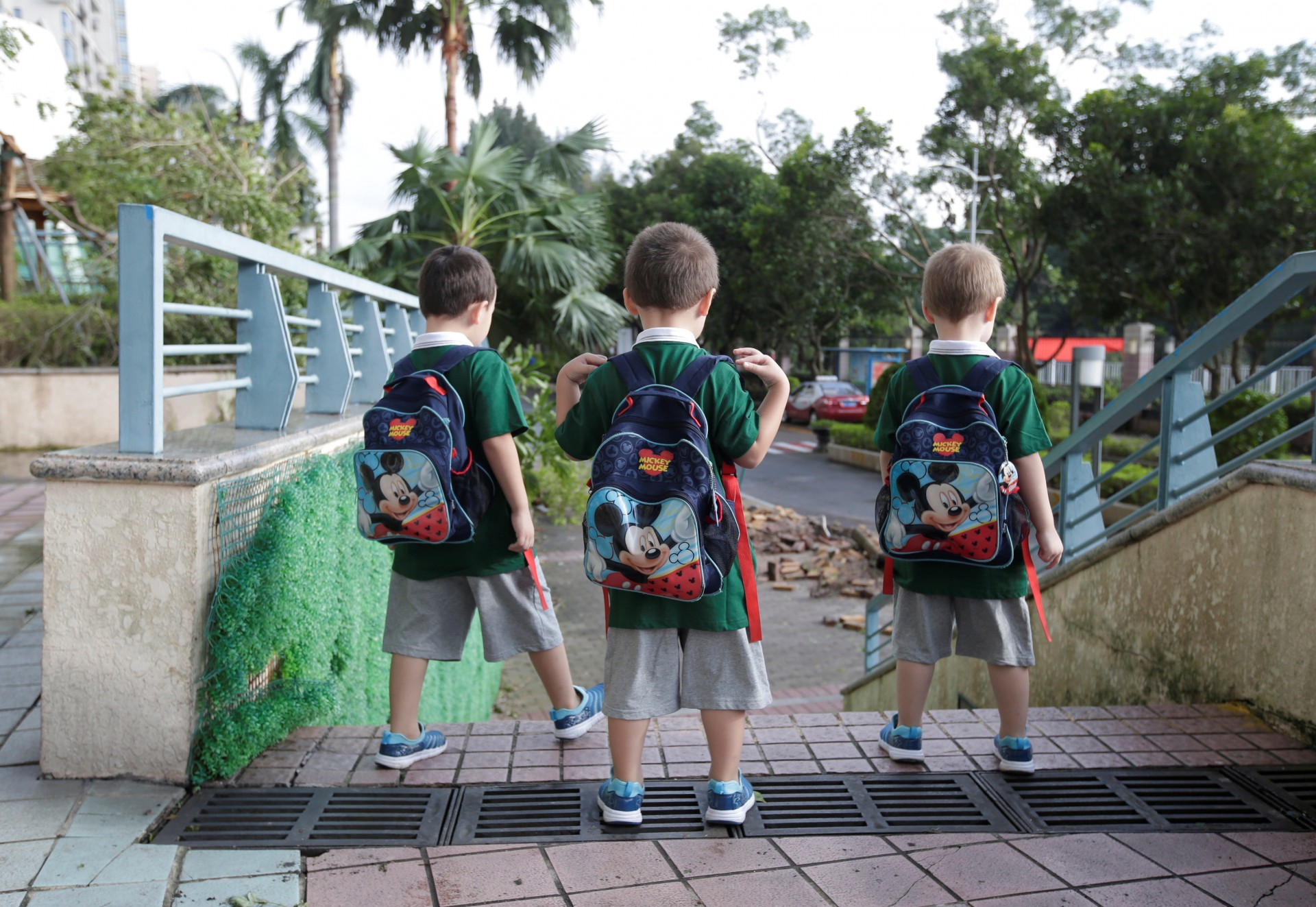 Los hijos de An Hui y Ye Jianbin, An Zhizhong, An Zhifei y An Zhiya, caminan al jardín de niños en Shenzhen.