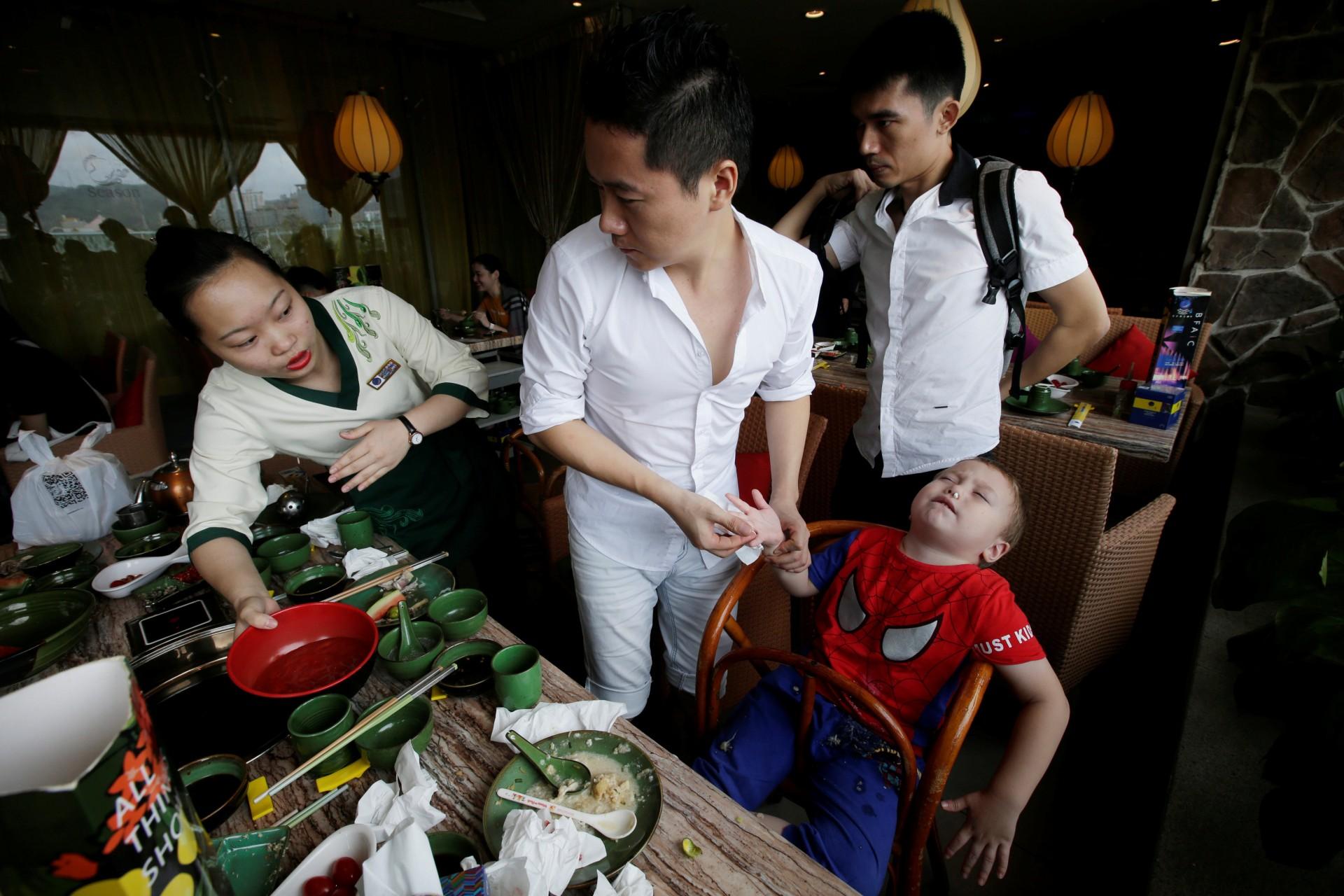 Un camarero ayuda a An Hui y su compañero Ye Jianbin con uno de sus hijos. An Zhiya sufre una hemorragia nasal después de un almuerzo en un restaurante en Shenzhen, provincia de Guangdong, China, el 17 de septiembre de 2018.