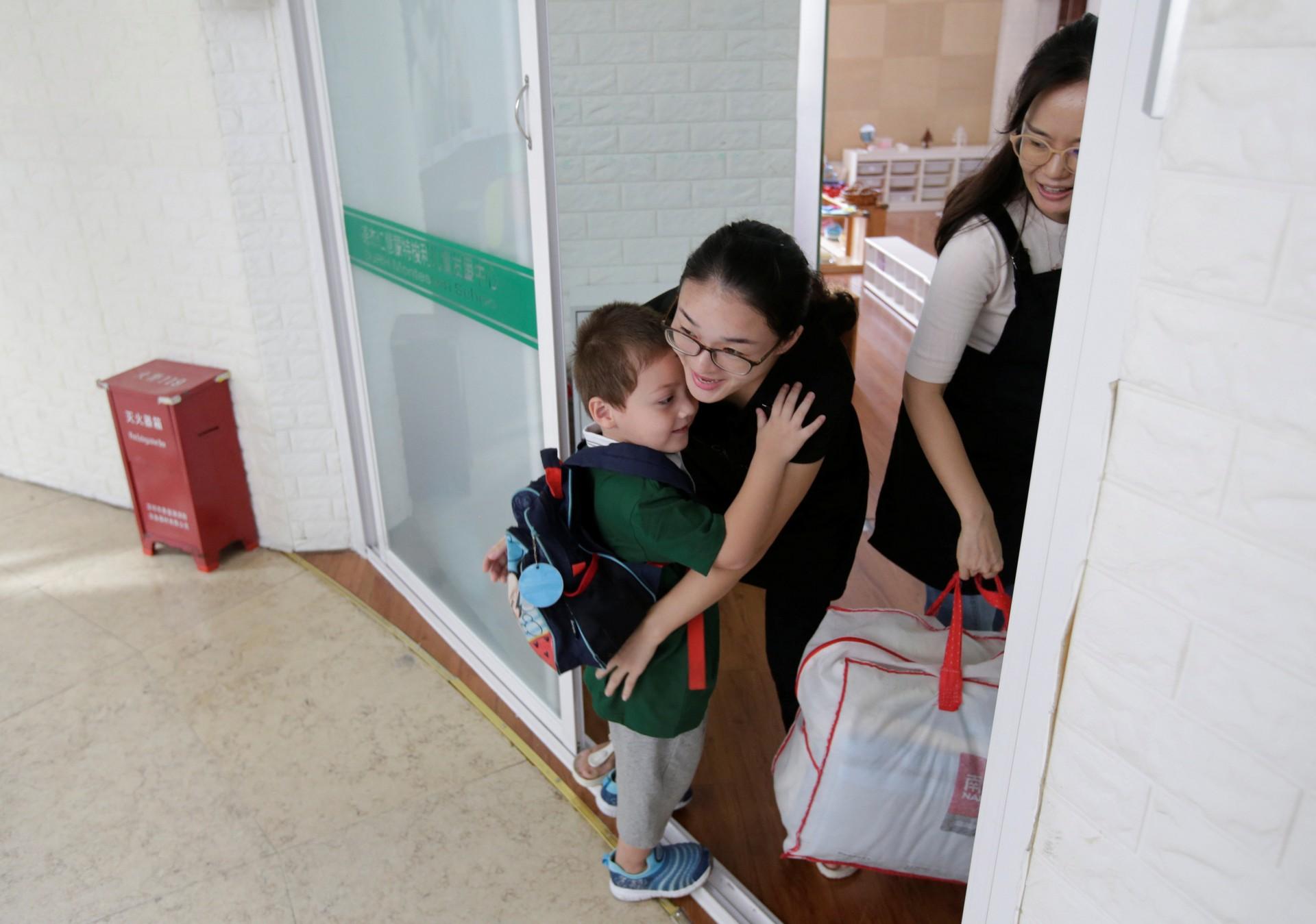 An Zhifei, uno de los tres hijos de An Hui y Ye Jianbin, abraza a su maestro cuando él y sus hermanos llegan a un jardín de infantes en Shenzhen.