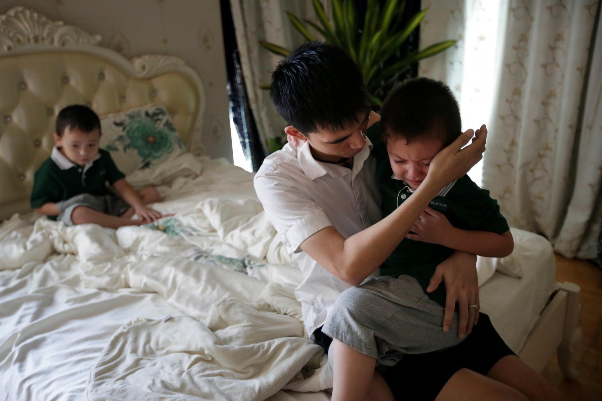 El compañerode An Hui, Ye Jianbin, apacigua a An Zhifei, uno de sus tres hijos.