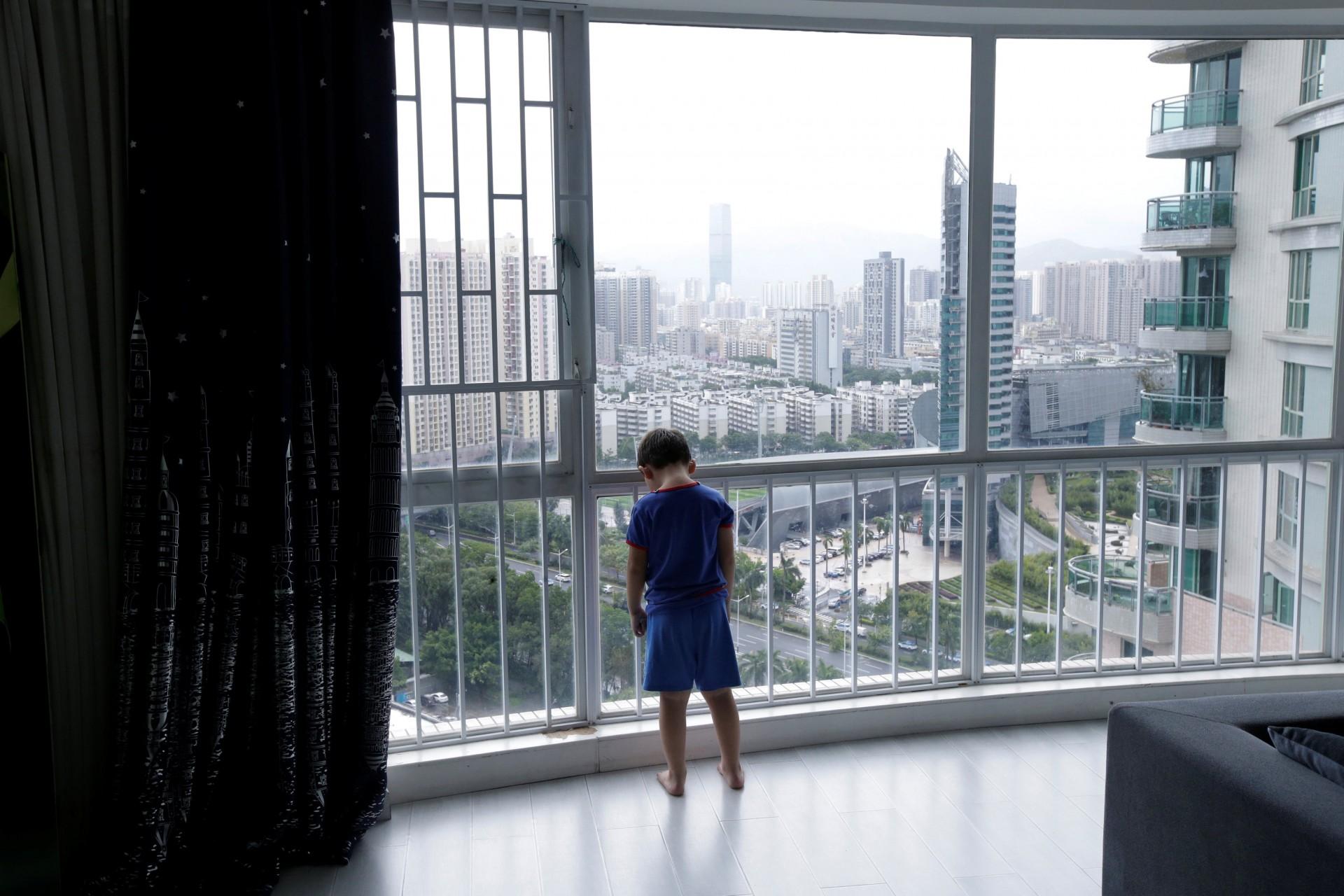 An Zhizhong, uno de los tres hijos de An Hui y Ye Jianbin, está parado junto a una ventana en su casa en Shenzhen, provincia de Guangdong, China, el 17 de septiembre de 2018.