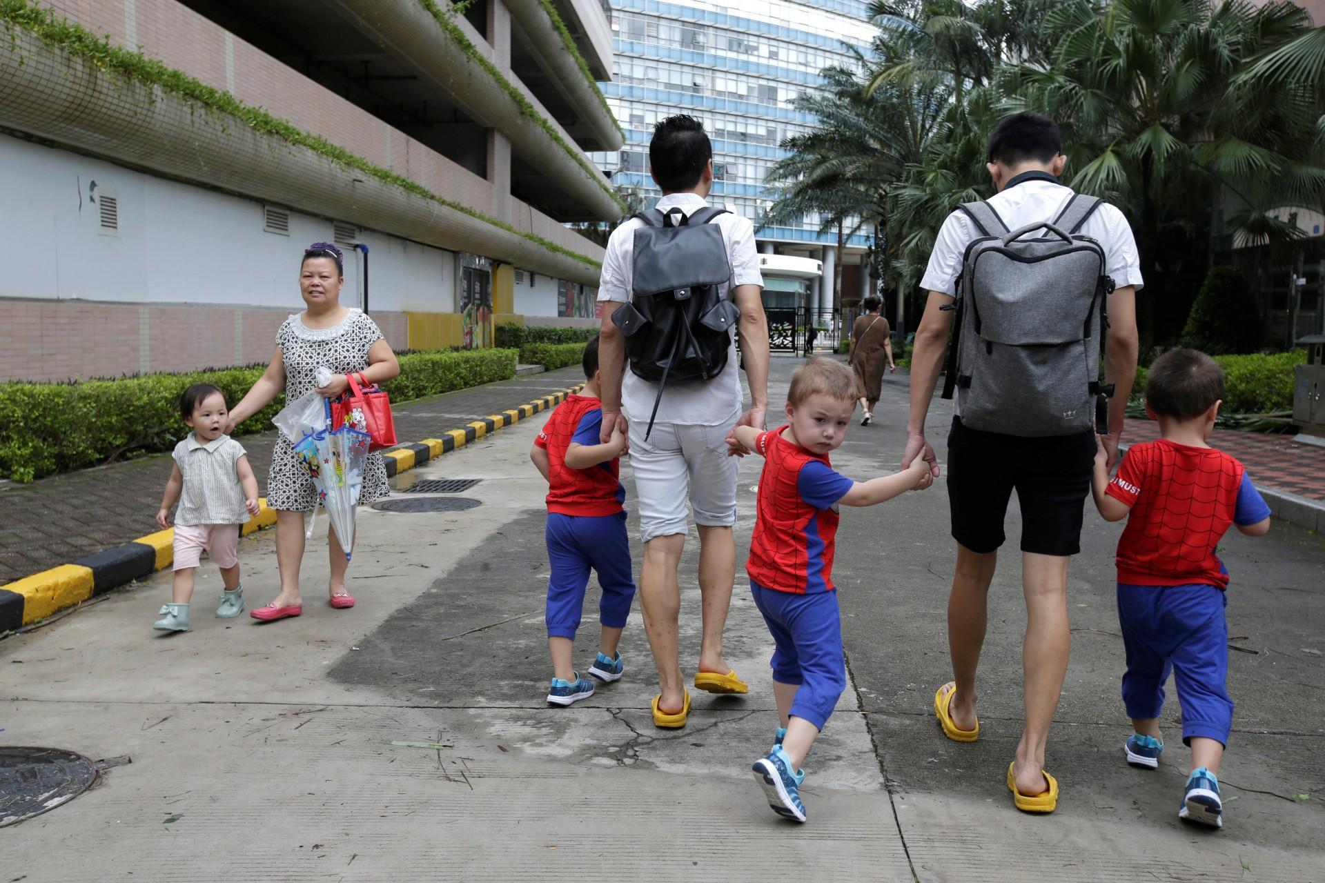 Una niña mira a An Hui y su compañero Ye Jianbin caminando con sus hijos, An Zhizhong, An Zhiya y An Zhifei en una comunidad residencial en Shenzhen, provincia de Guangdong, China, 17 de septiembre de 2018.