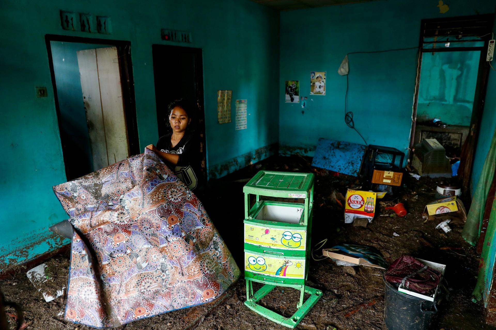 Una mujer busca entre pertenecer a su casa, que fue golpeada por el tsunami en Pandeglang, provincia de Banten, Indonesia, 24 de diciembre de 2018.