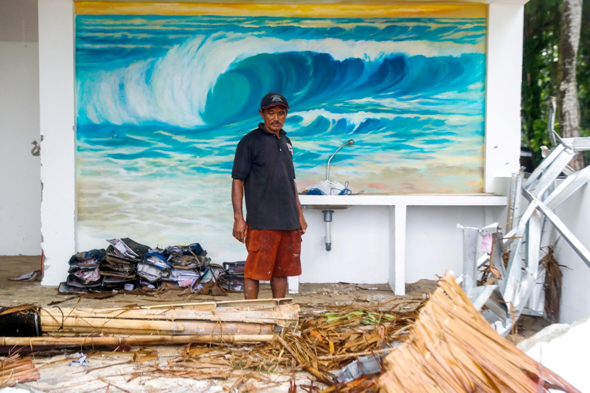Un trabajador se para frente a un mural dentro de un bar en un complejo destruido que fue golpeado por un tsunami en Tanjung Lesung, provincia de Banten, Indonesia, Indonesia, 24 de diciembre de 2018.