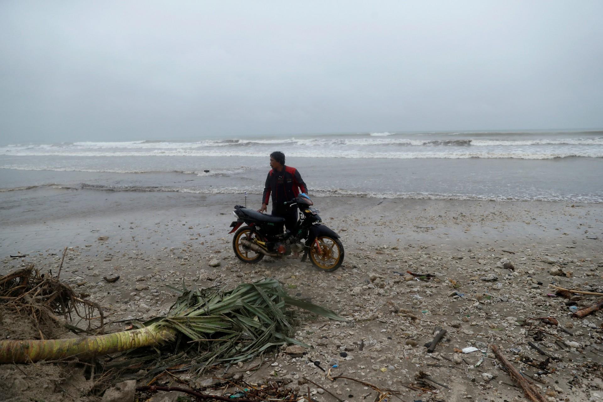 Un hombre está parado junto a una motocicleta en una playa azotada por un tsunami, cerca de Sumur, provincia de Banten, Indonesia, 26 de diciembre de 2018.