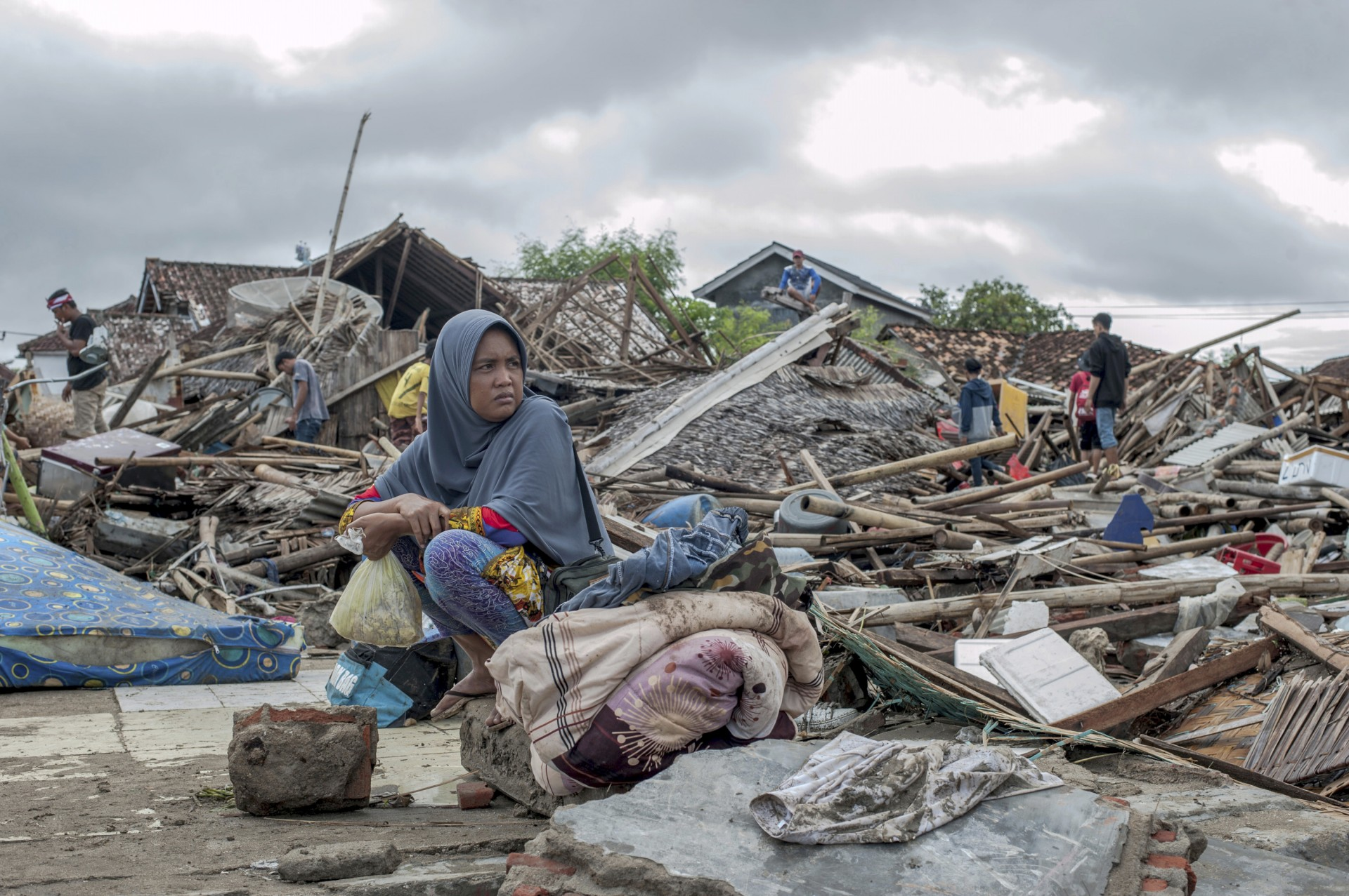 Una sobreviviente del tsunami se sienta en un pedazo de escombros mientras rescata artículos de la ubicación de su casa en Sumur, Indonesia, el lunes 24 de diciembre de 2018.