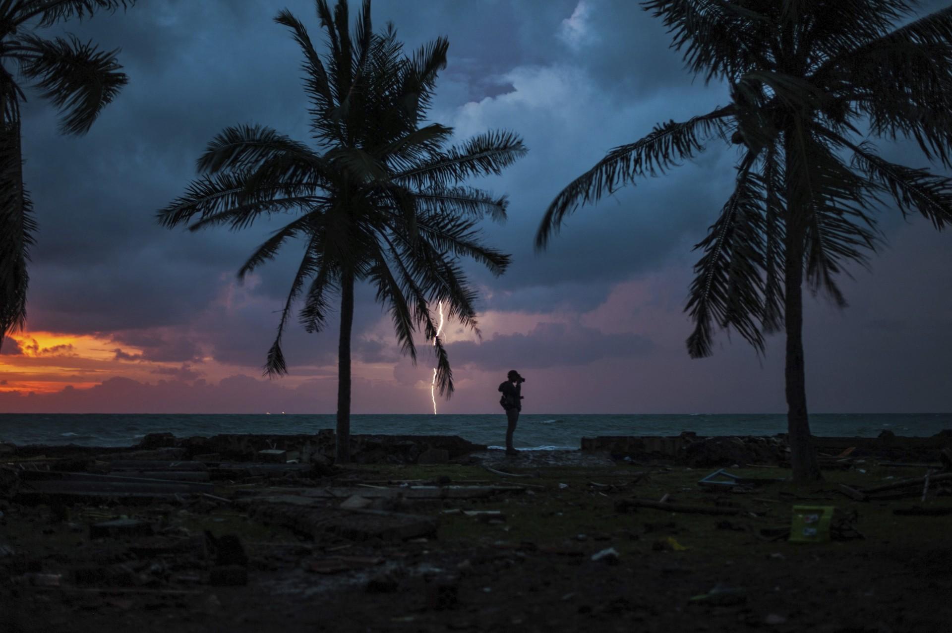 La puesta de sol siluetea a un reportero gráfico con un rayo en un centro turístico afectado por el tsunami del sábado en Indonesia, el martes 25 de diciembre de 2018.