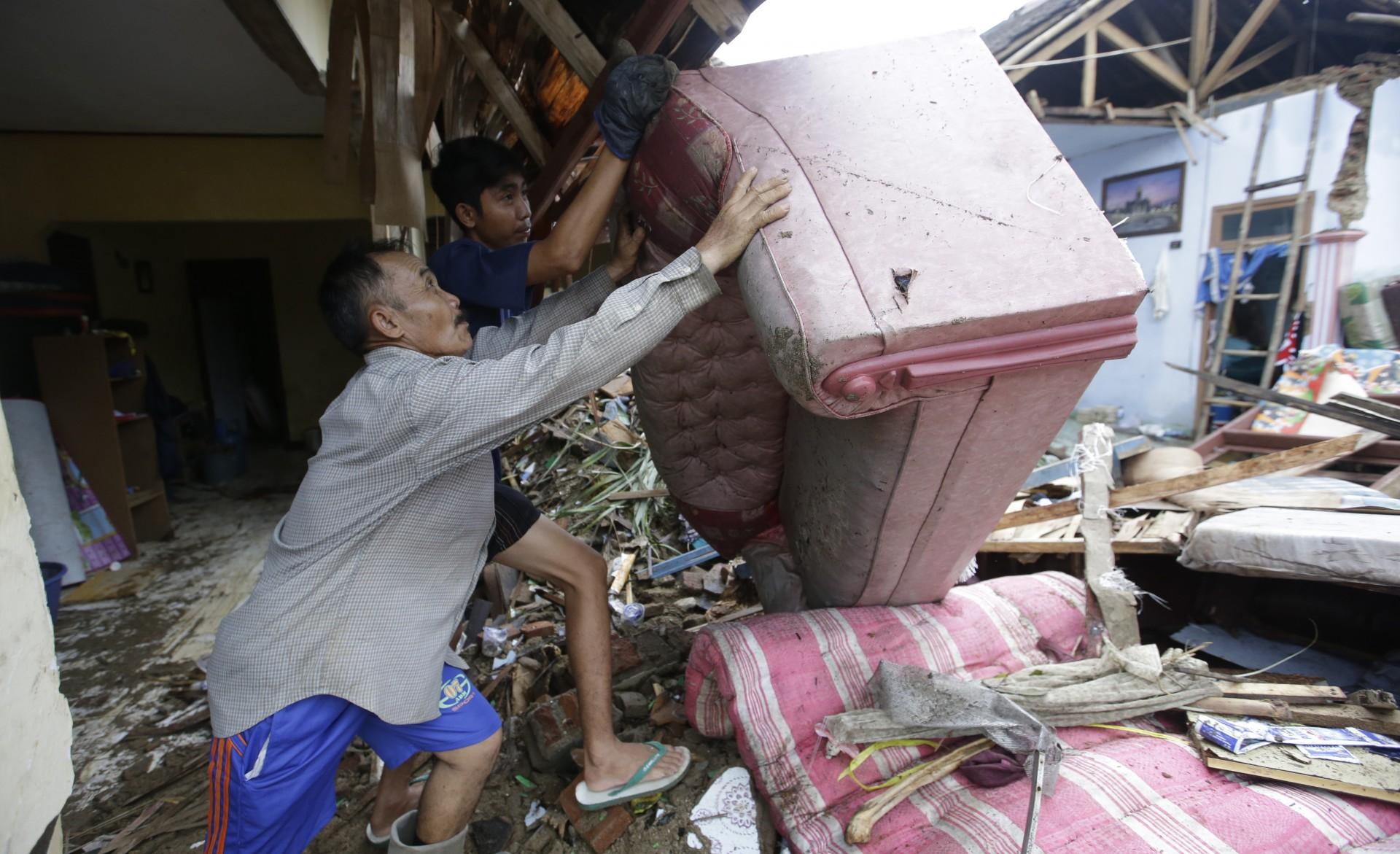 El residente local Alimin limpia los escombros de su casa luego del tsunami en Carita, Indonesia, el jueves 27 de diciembre de 2018.