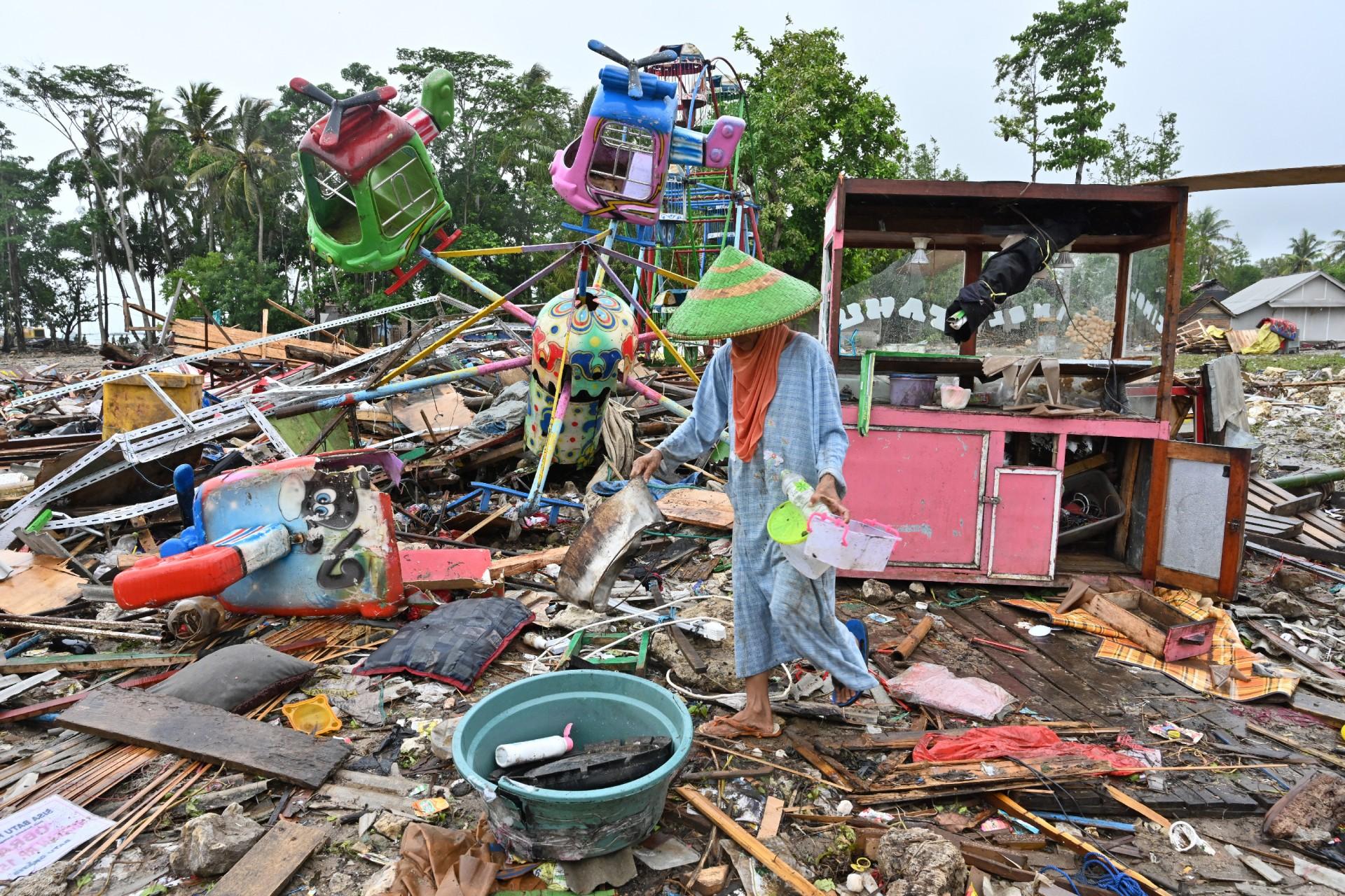 Una mujer rescata objetos de valor de un parque de diversiones temporal que fue golpeado por un tsunami en la aldea de Sumber Jaya en Sumur, Pandeglang, provincia de Banten, el 25 de diciembre de 2018.
