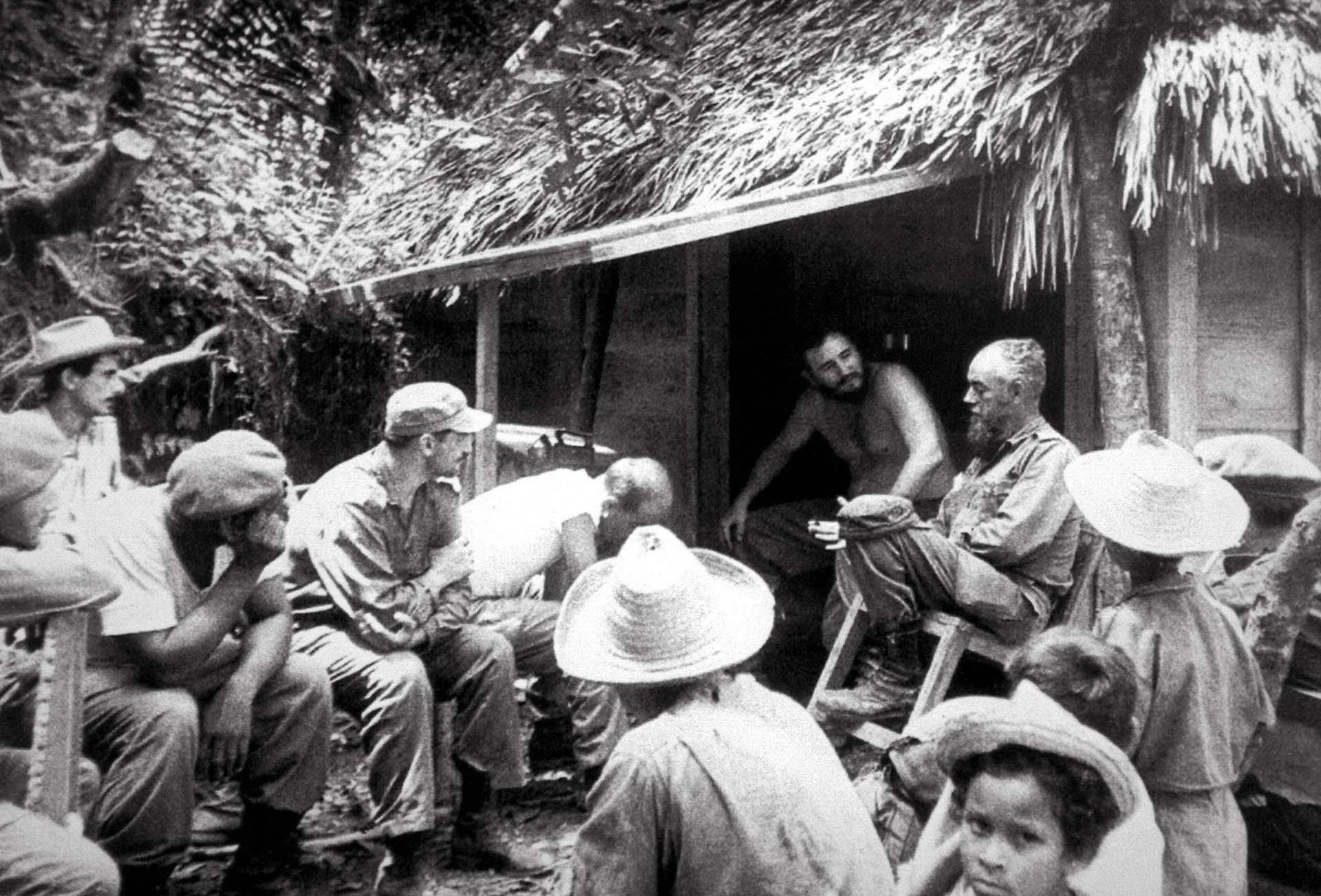 Fidel Castro, sin camiseta, conversa con milicianos y granjeros durante los días de la reforma agraria y la expropiación de tierras, en mayo de 1959