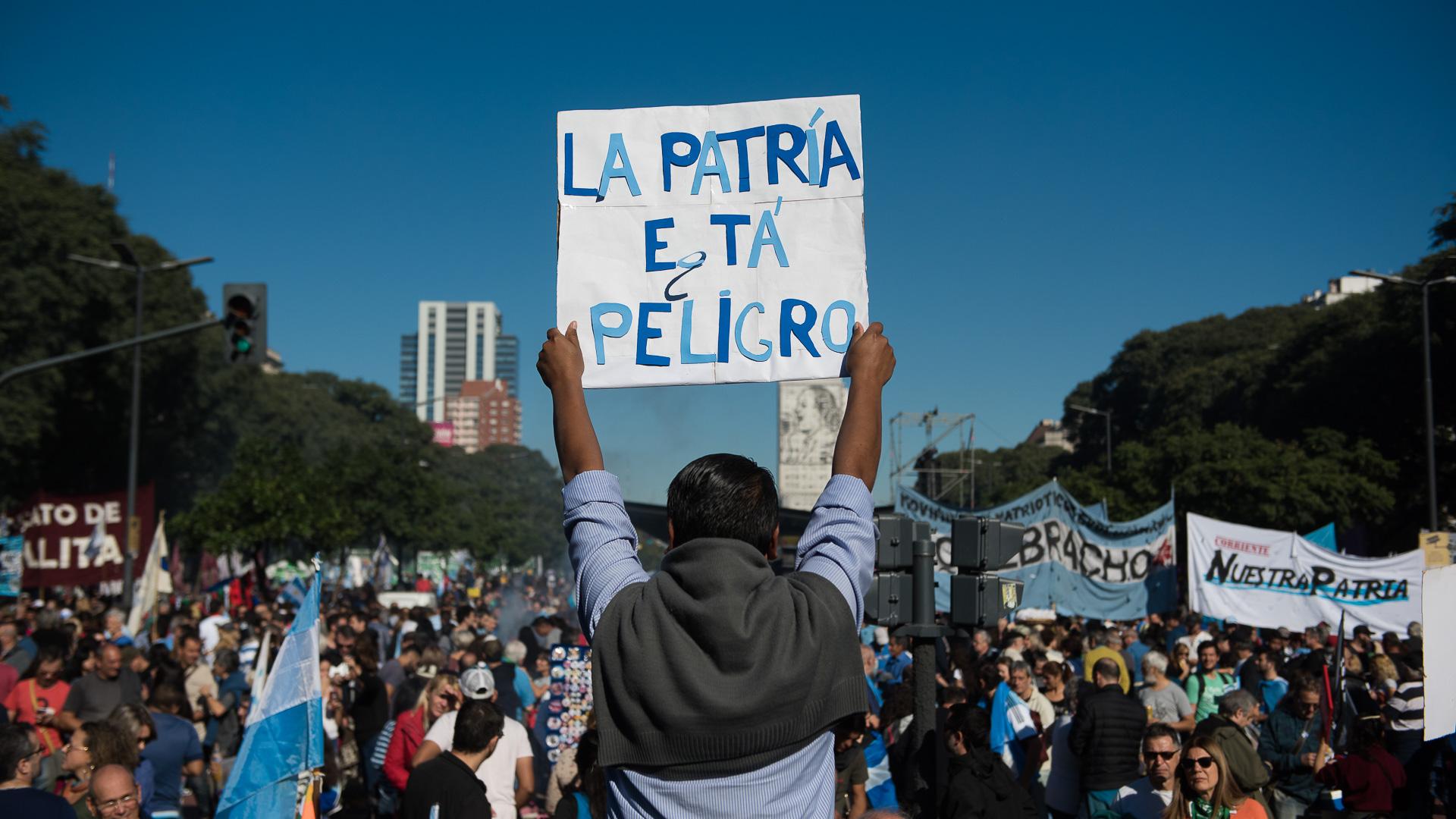 """Una persona muestra un cartel con la leyenda """"La Patria está en Peligro"""" durante la marcha en conmemoración a la Revolución de Mayo (Adrián Escandar)"""
