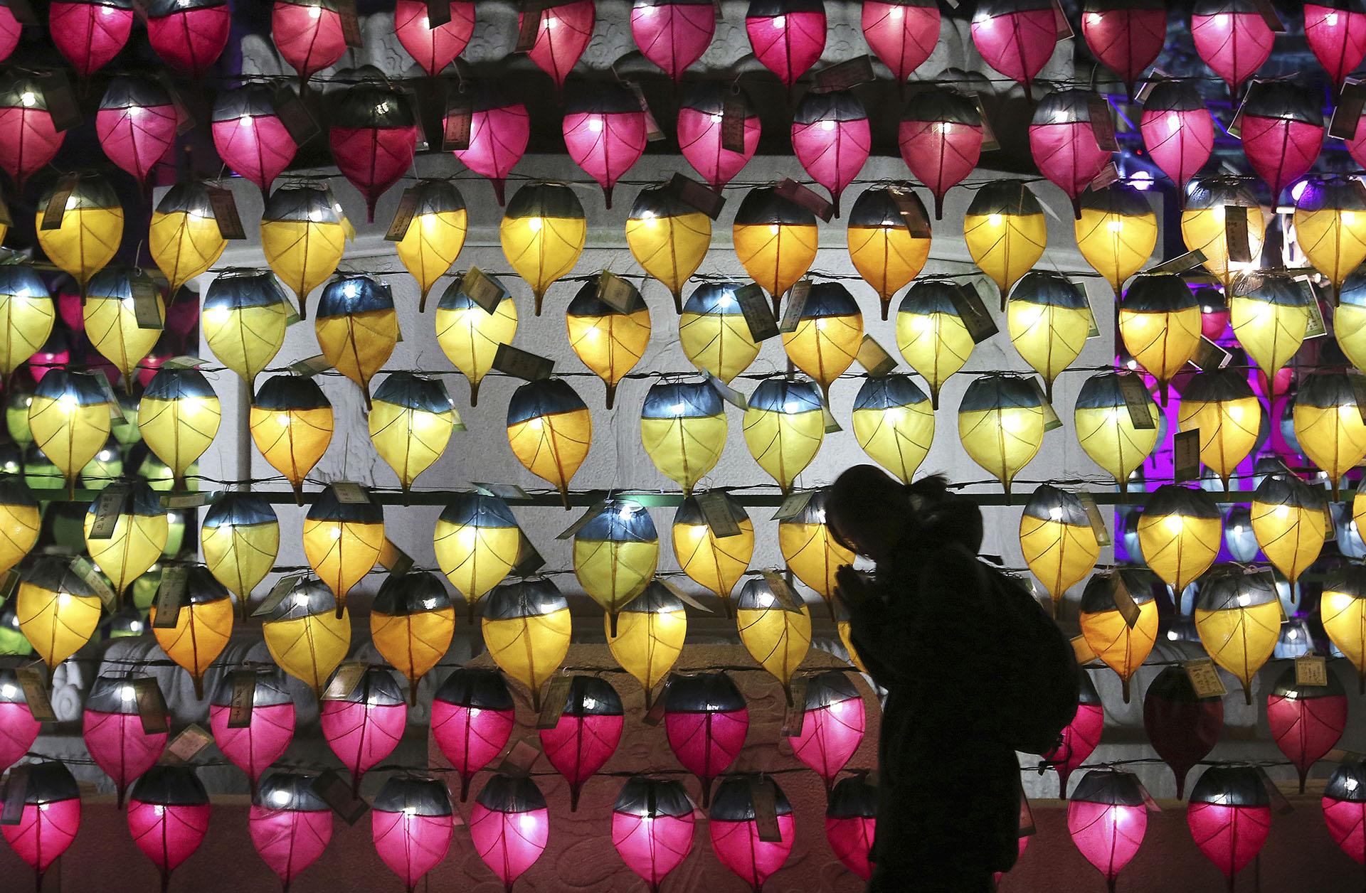 Una mujer reza frente a las lámparas iluminadas con velas en un templo budista de Seúl