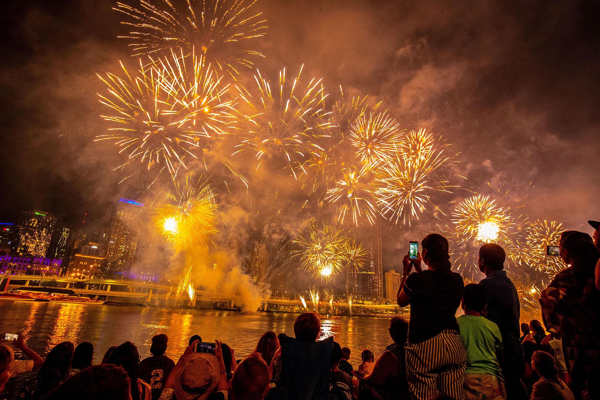 La gente ve los primeros fuegos artificiales antes de la víspera de Año Nuevo sobre el río Brisbane en Southbank en Brisbane, Queensland, Australia