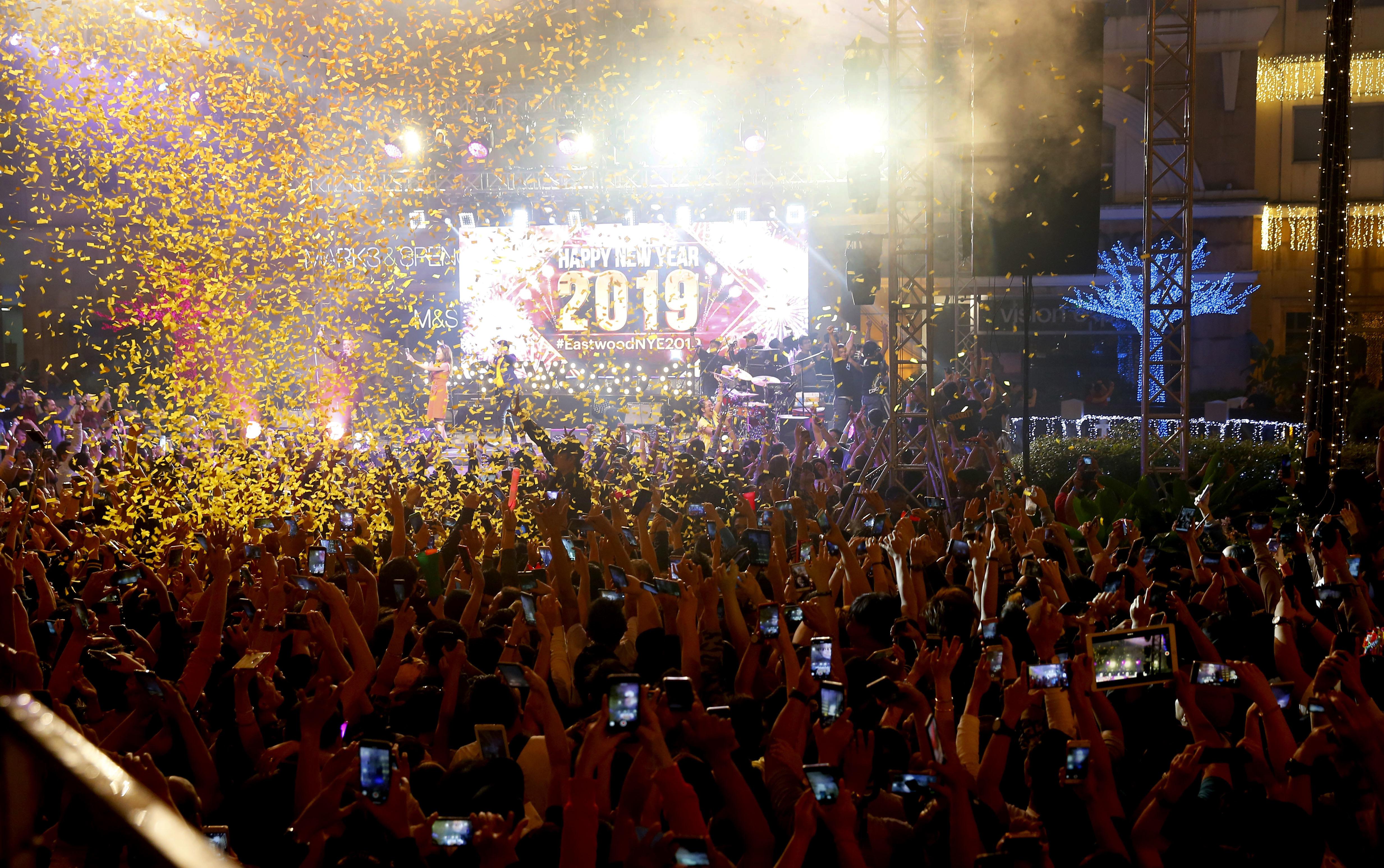 Una lluvia de confeti cae sobre los juerguistas en el centro comercial Eastwood que reciben el Año Nuevo (AP Foto/Bullit Marquez)
