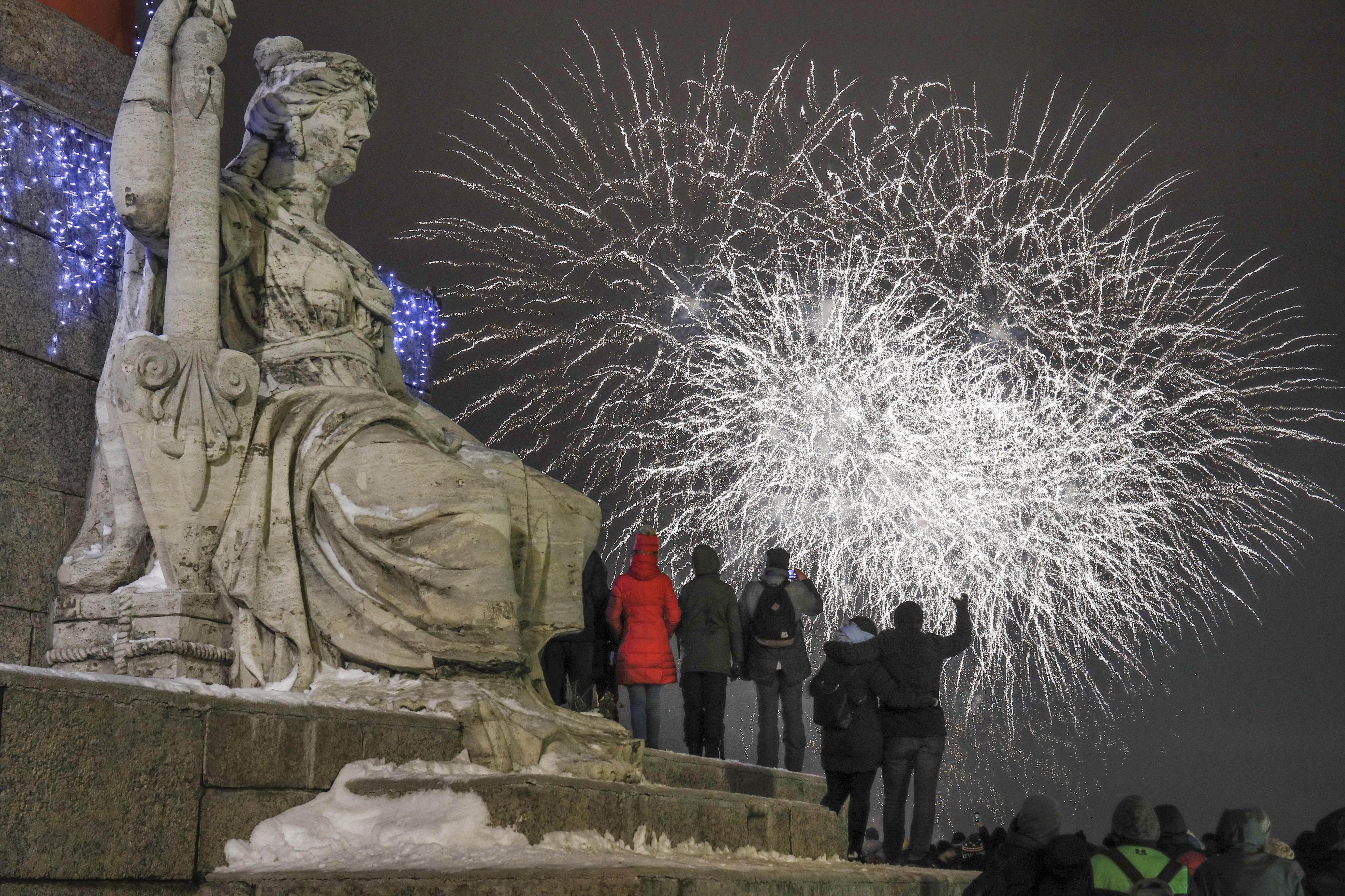 Varias personas observan los fuegos artificiales durante los festejos por el Año Nuevo en el centro de San Petersburgo(AP Foto/Dmitri Lovetsky)